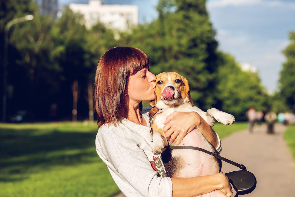 Girl in park kissing her beagle
