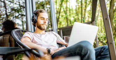 This image depicts a man relaxing outdoors with his laptop.