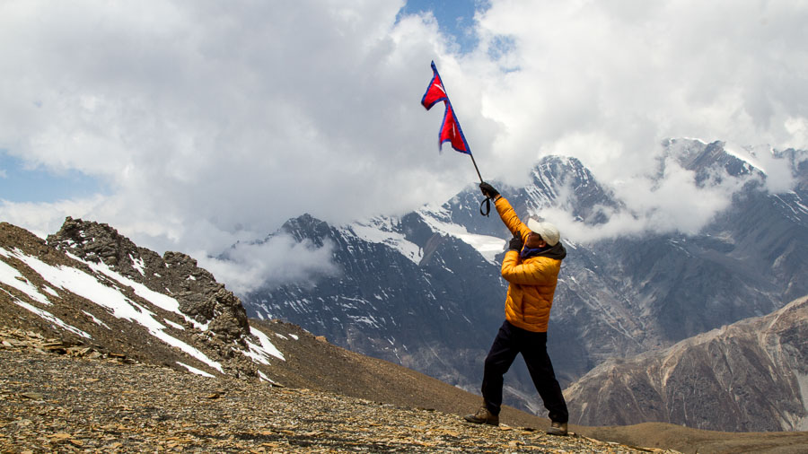 Tripple P Gurung raises the Nepali flag on top of the Naar Pass.