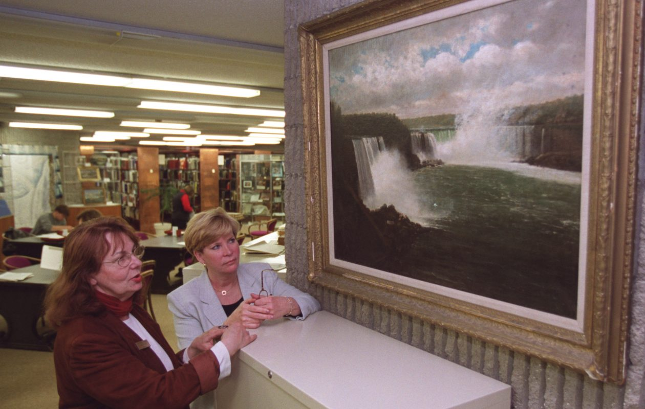 In this photo from 2000, Maureen Fennie, head of the Local History Department of the Niagara Falls Public Library, and Library Director Betty Babanoury, look at a small version of a larger painting that is missing.  The large painting was done in 1893 by Patrick C. Flynne, a famous Niagara Falls artist. It was loaned to the state Capitol, from which it vanished. (Buffalo News file photo)