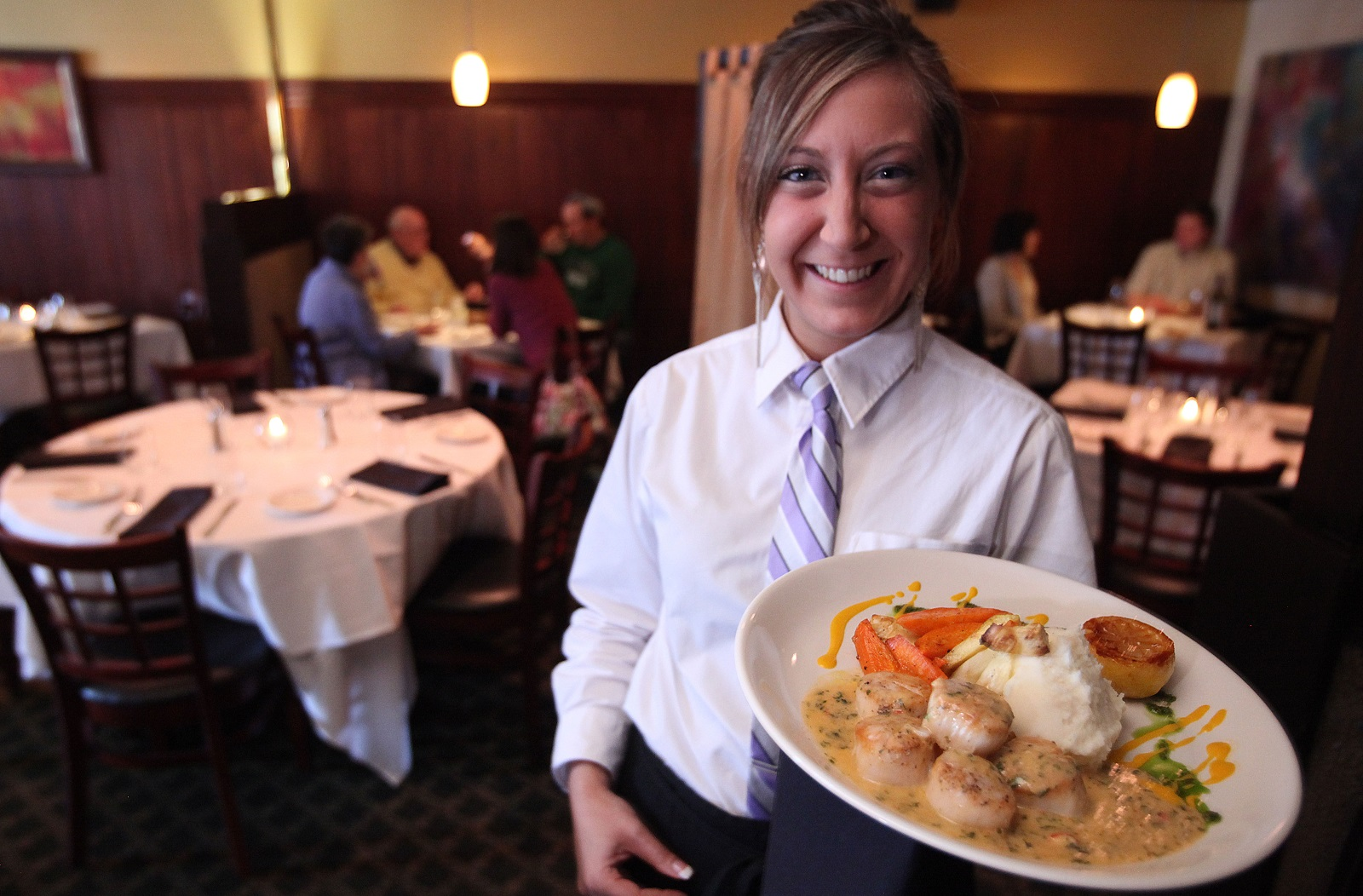 Server Jennifer Arnone offers scallops in the dining room at Protocol Restaurant. (Buffalo News file photo)