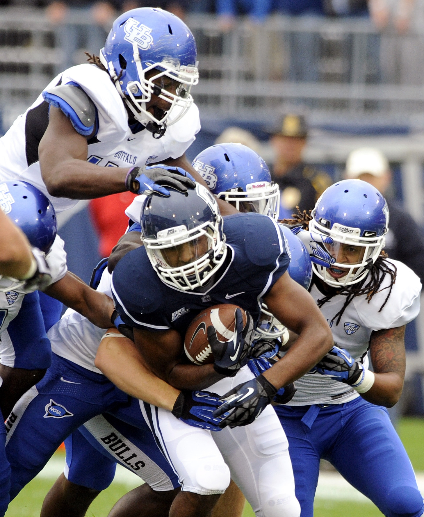 Associated Press    Connecticut tailback Lyle McCombs is gang tackled by a swarm of UB defenders in the first half of the Bulls' 24-17 loss to UConn on Saturday.