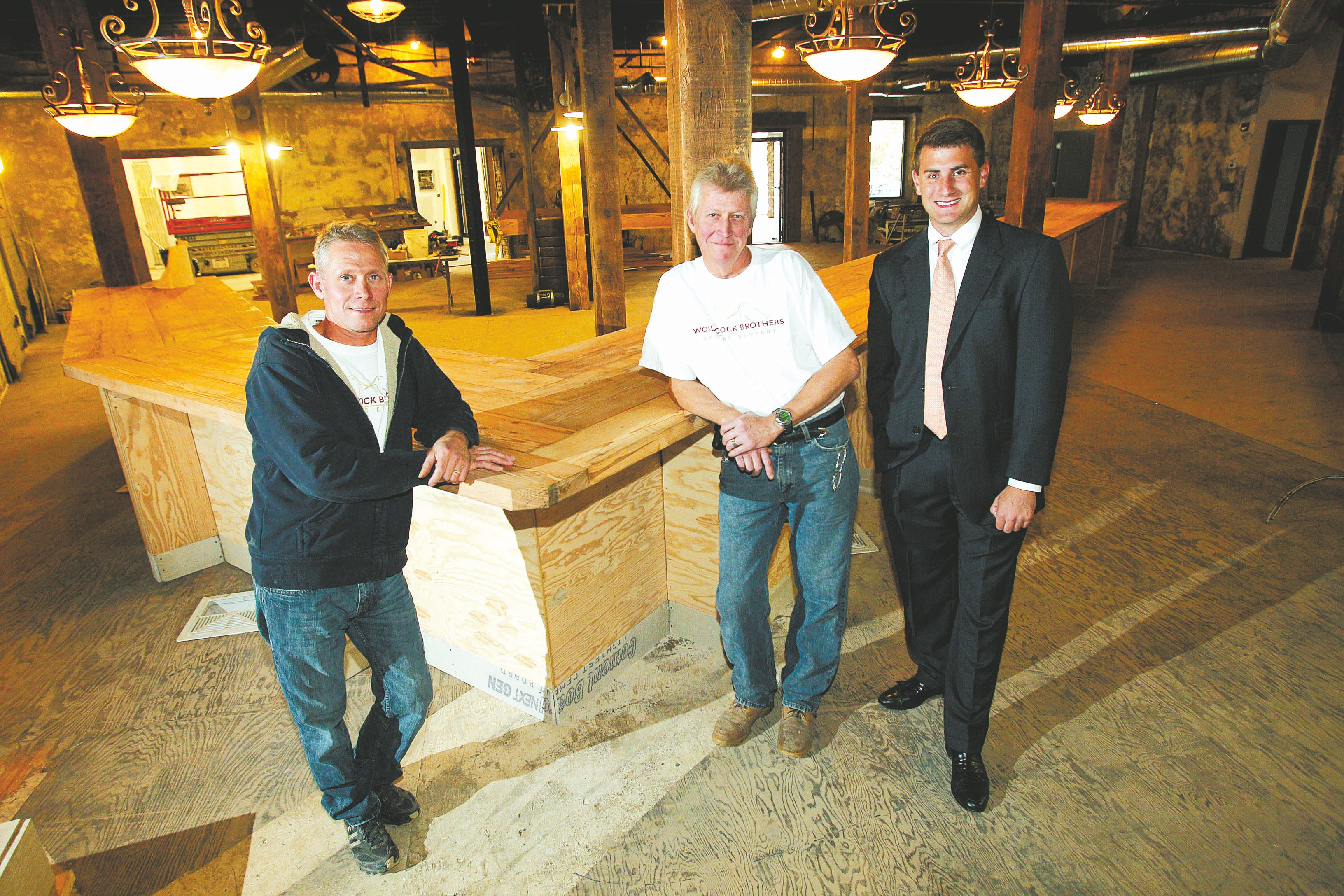 Brothers Tim Woodcock, left, and Mark Woodcock, center, got a loan from M&T for their brewery, Woodcock Brothers Brewing Co. in Wilson. With them is Jerome Baier of M&T Bank.