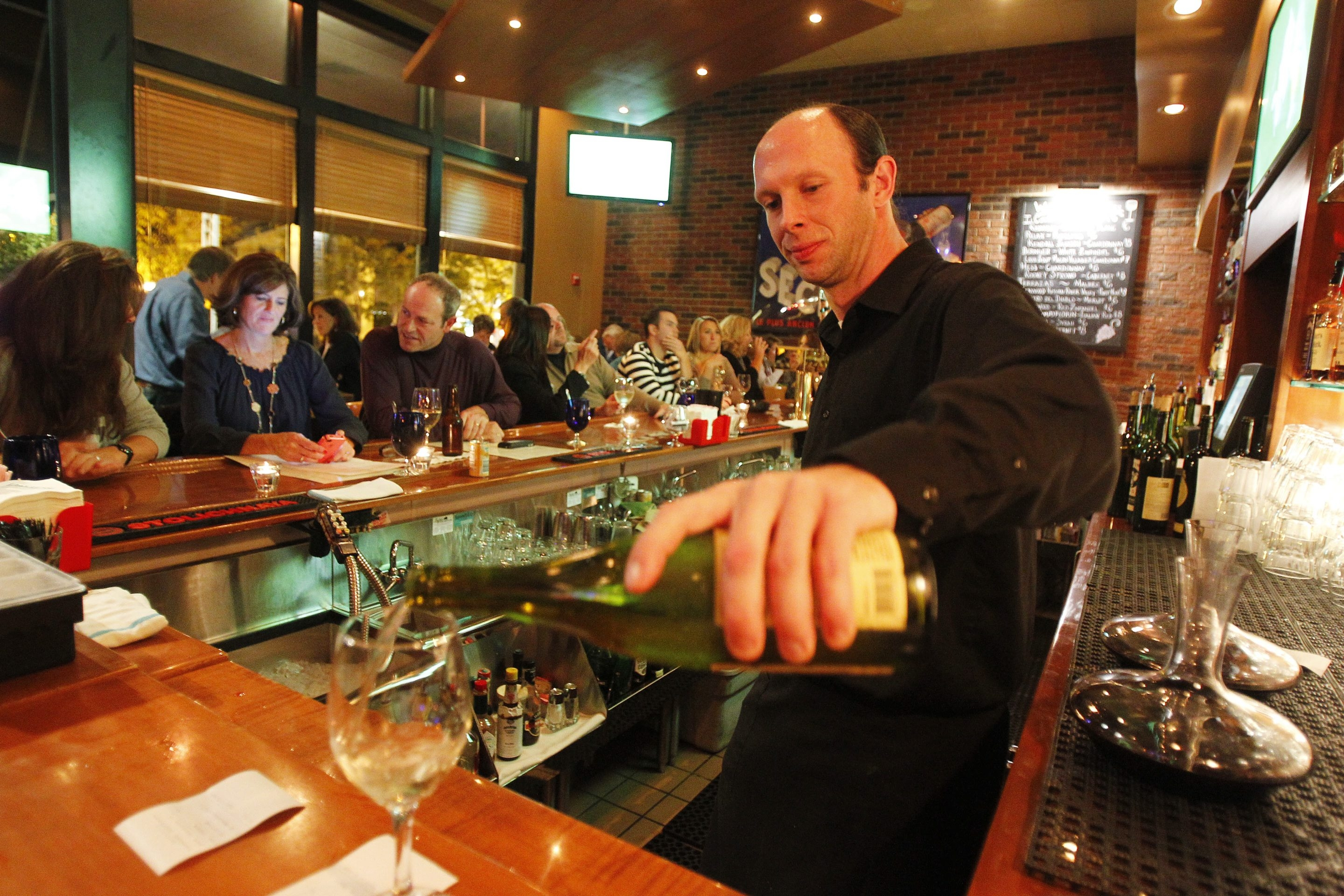 Mark Mulville/Buffalo News    Manager Jeremy Ryan pours a glass of wine at David's Grille in Orchard Park.