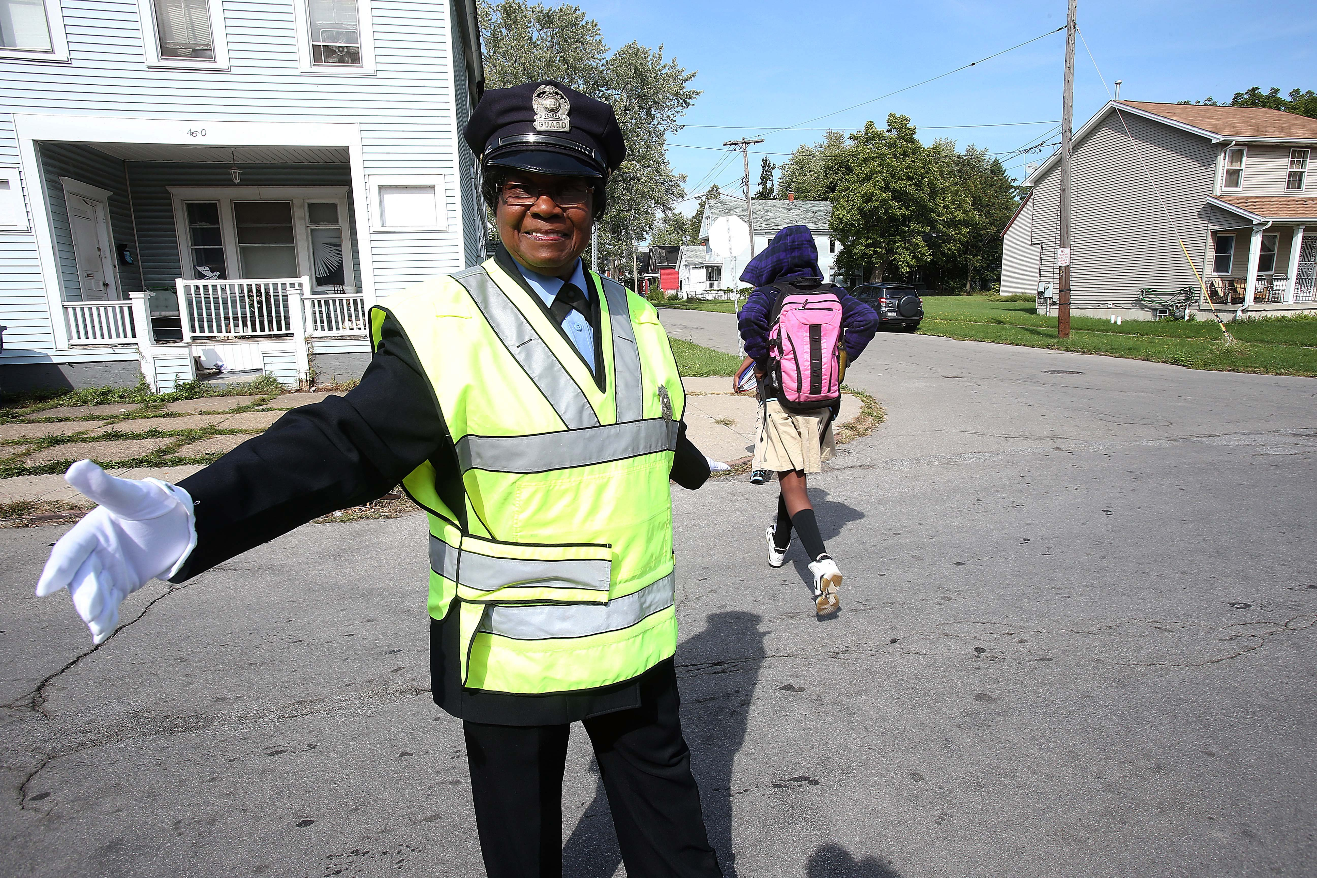 Buffalo crossing guard Jane L. Ervin, 86, helps a student cross the street outside Martin Luther King Multicultural Institute School 39 on Tuesday. She has spent the past 60 years manning posts near city schools.    Robert Kirkham/Buffalo News