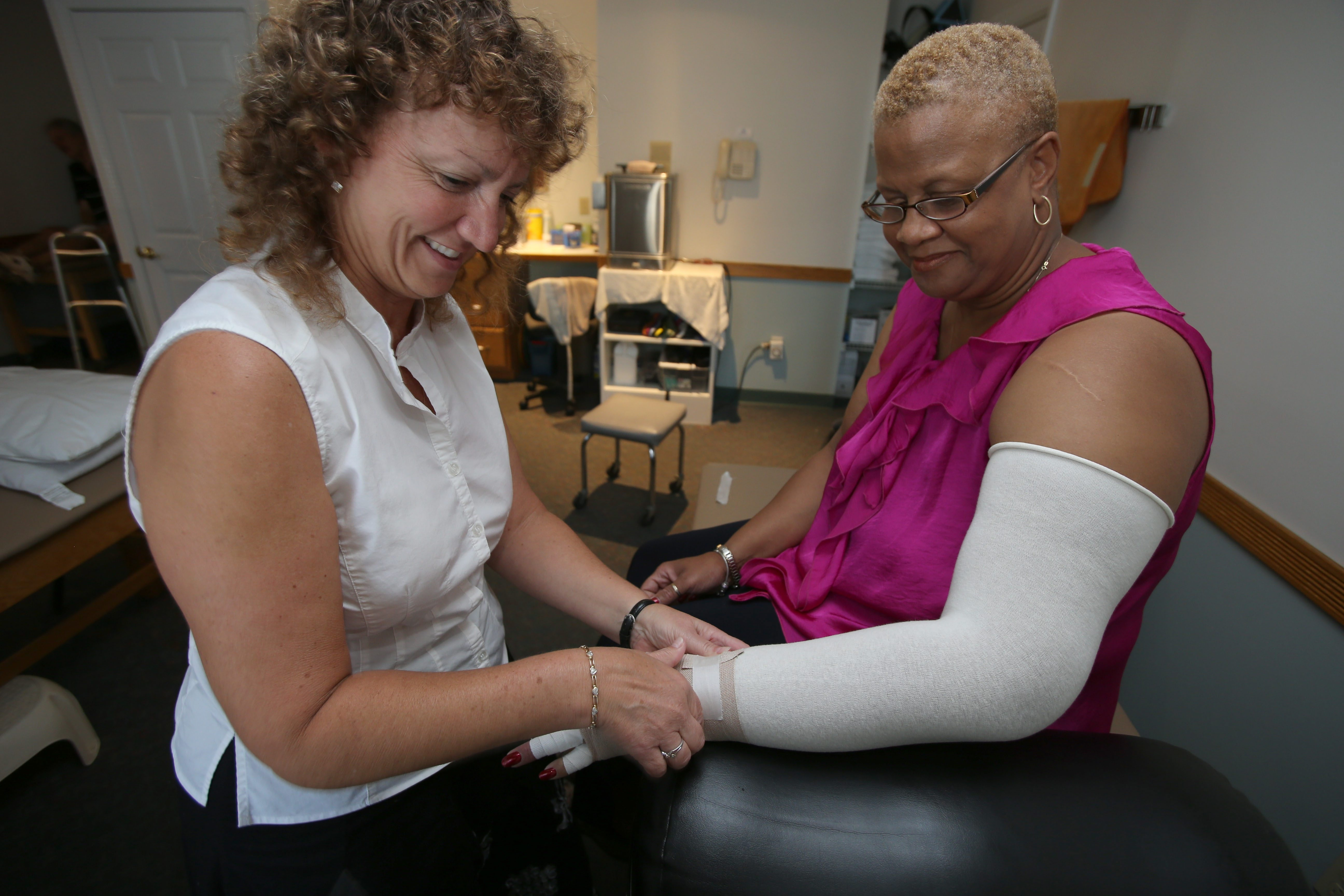 Charles Lewis/Buffalo News    Donna Gulick, a doctor of physical therapy, left, wraps Pleasant Millsap-Mack's arm at Ortho Sports Physical Therapy in Snyder on Thursday.  The wraps control swelling from lymphedema.