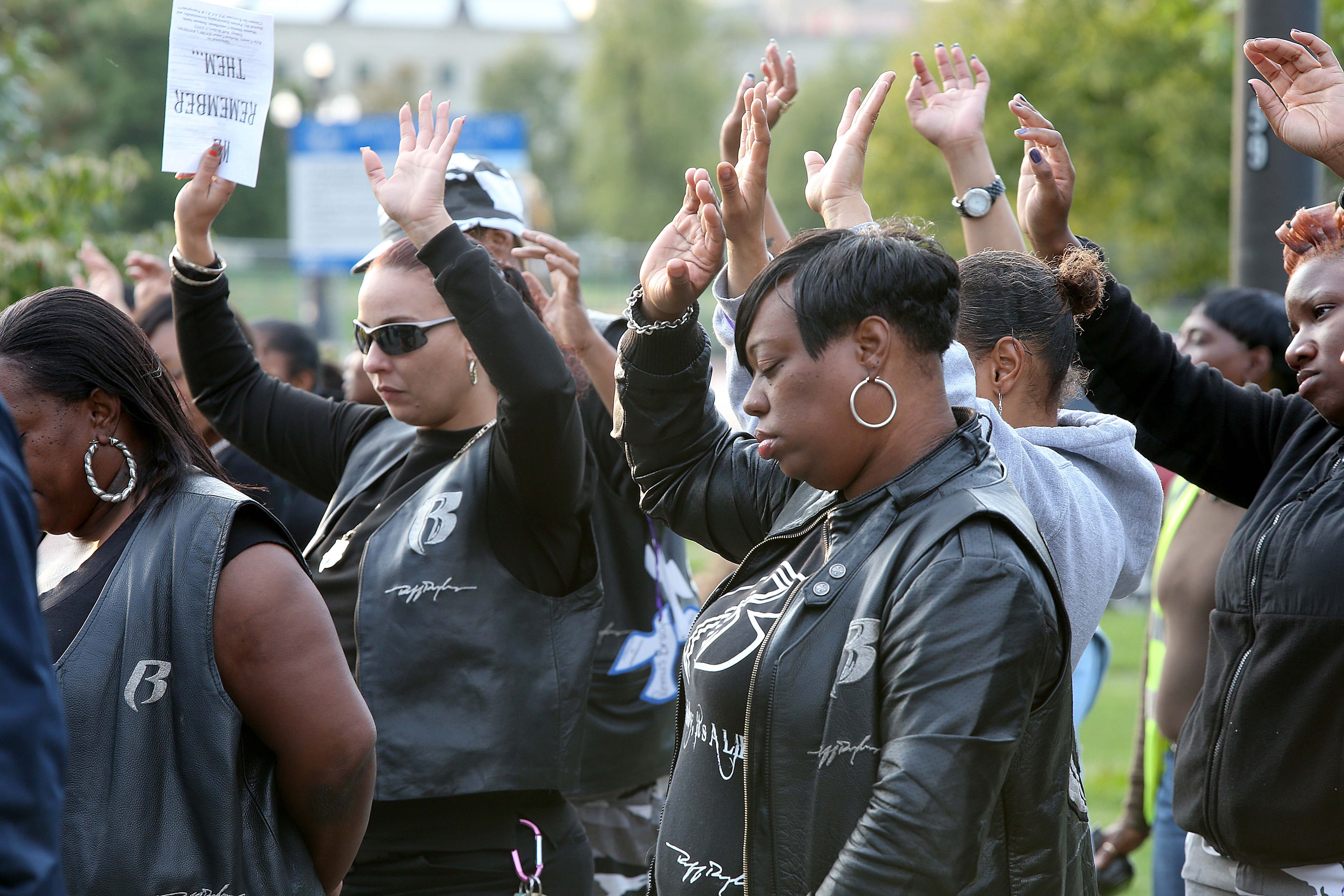 Robert Kirkham/Buffalo News    Sylvia Bryant, right, prays for her mother, Latefya Lewis, who was stabbed to death in 2005, during a remembrance for murder victims held at Martin Luther King Jr. Park.