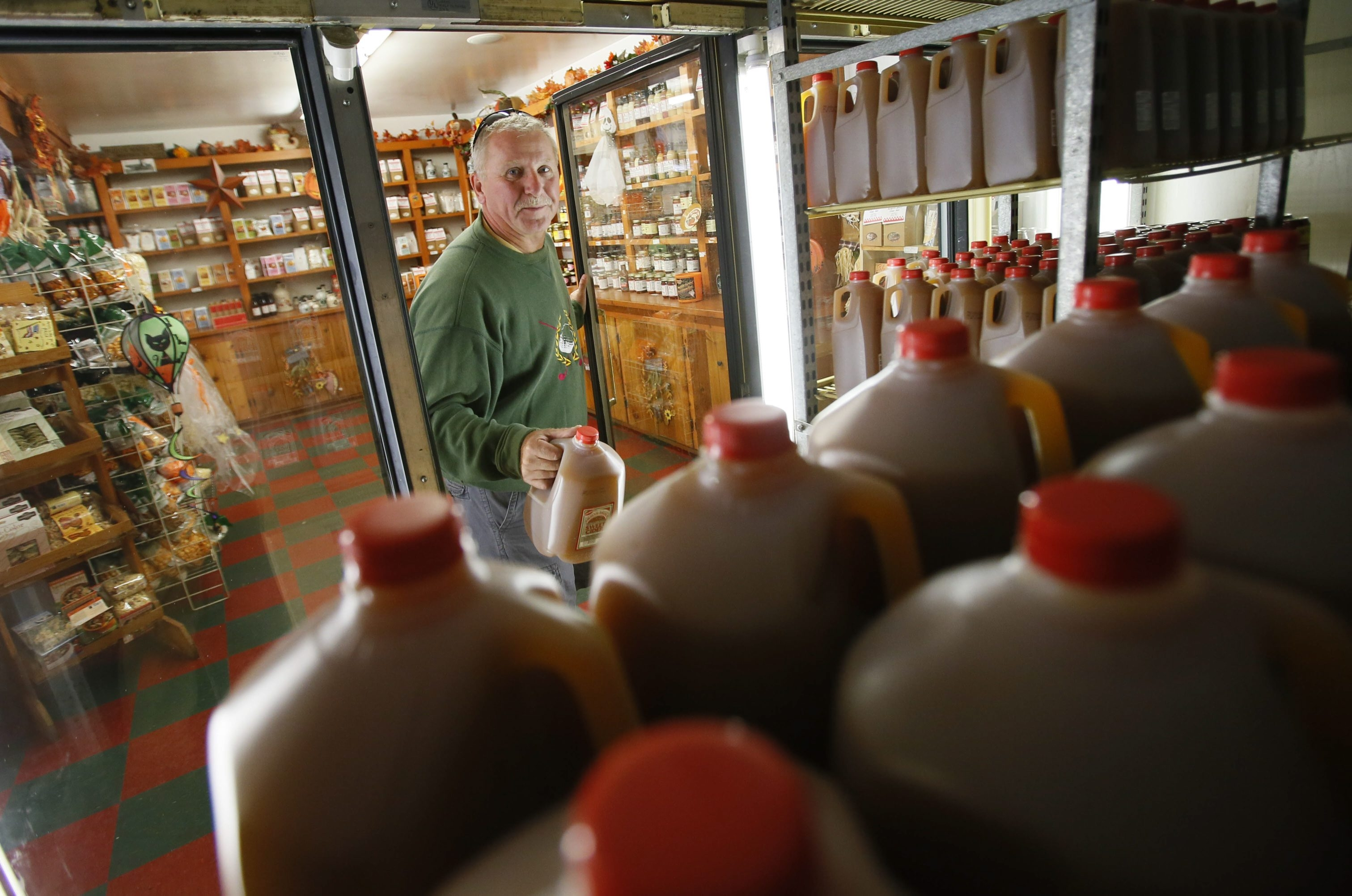 Jim Sypniewski, of West Seneca, picks up some cider from the cooler at the Mayer Brothers store in the town, perpetuating a Western New York tradition that has flourished since family patriarch Jacob Mayer established his mill there in 1852.