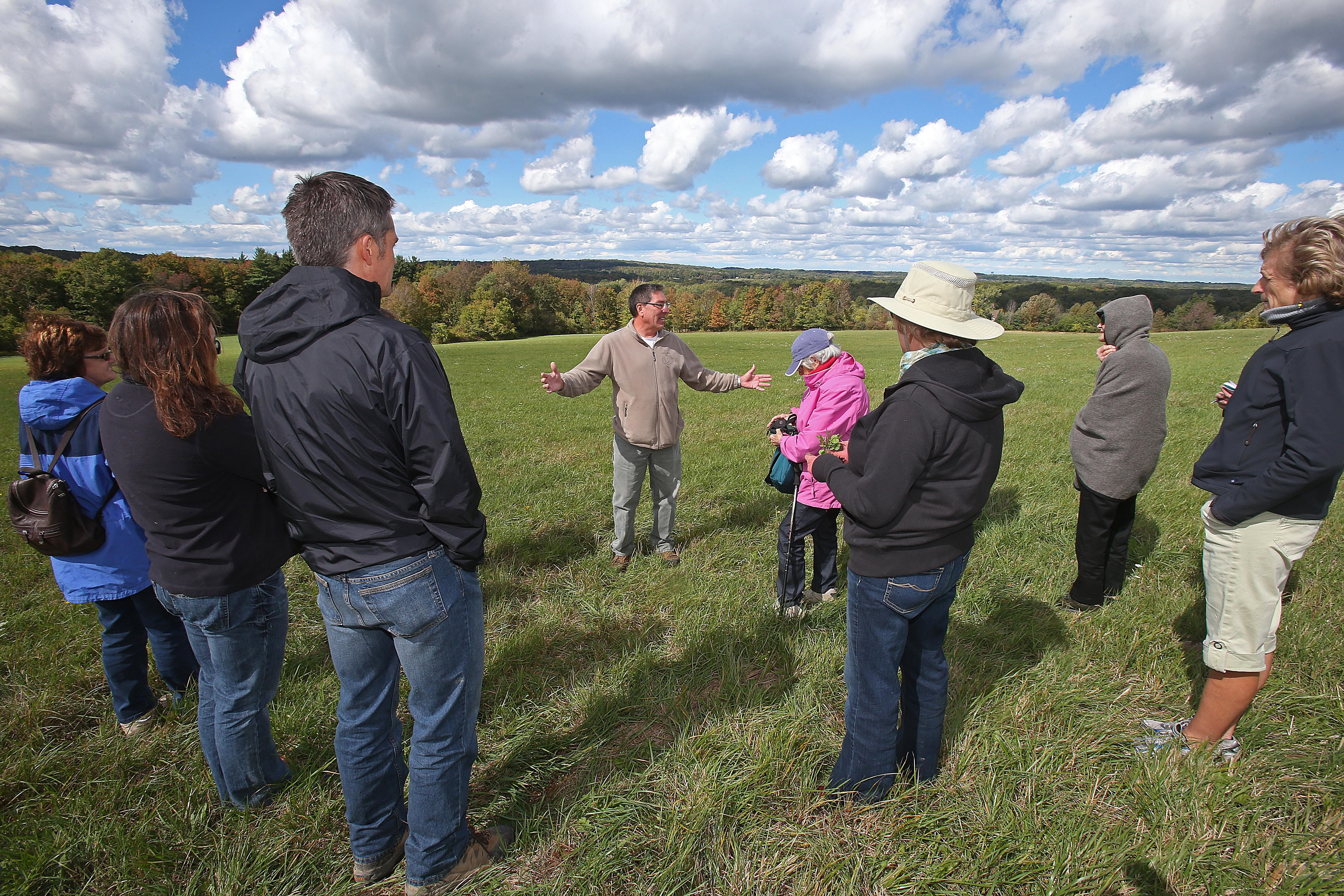Robert Kirkham/Buffalo News    Native plant specialist Ken Parker, center, stops to talk about grasslands during a walking tour of the Mill Road site in Aurora on Sunday.