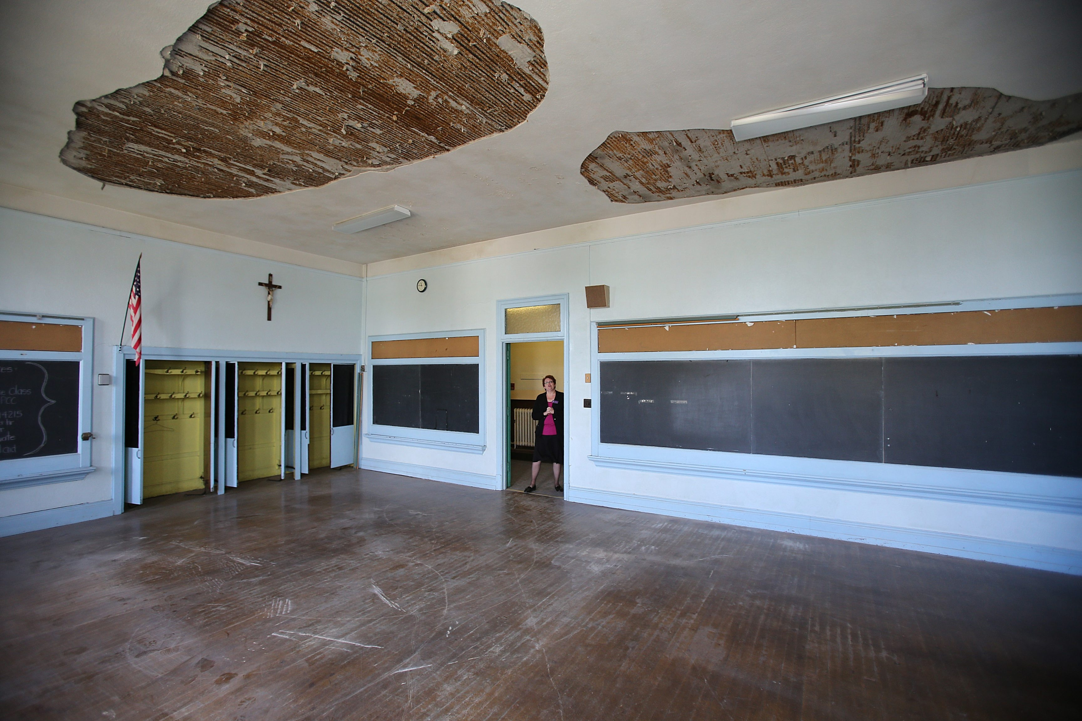 Charles Lewis/Buffalo News    Volunteer Kelli Cavo looks into a  vacant classroom Sunday in the former St. Gerard parish hall on Bailey Avenue.