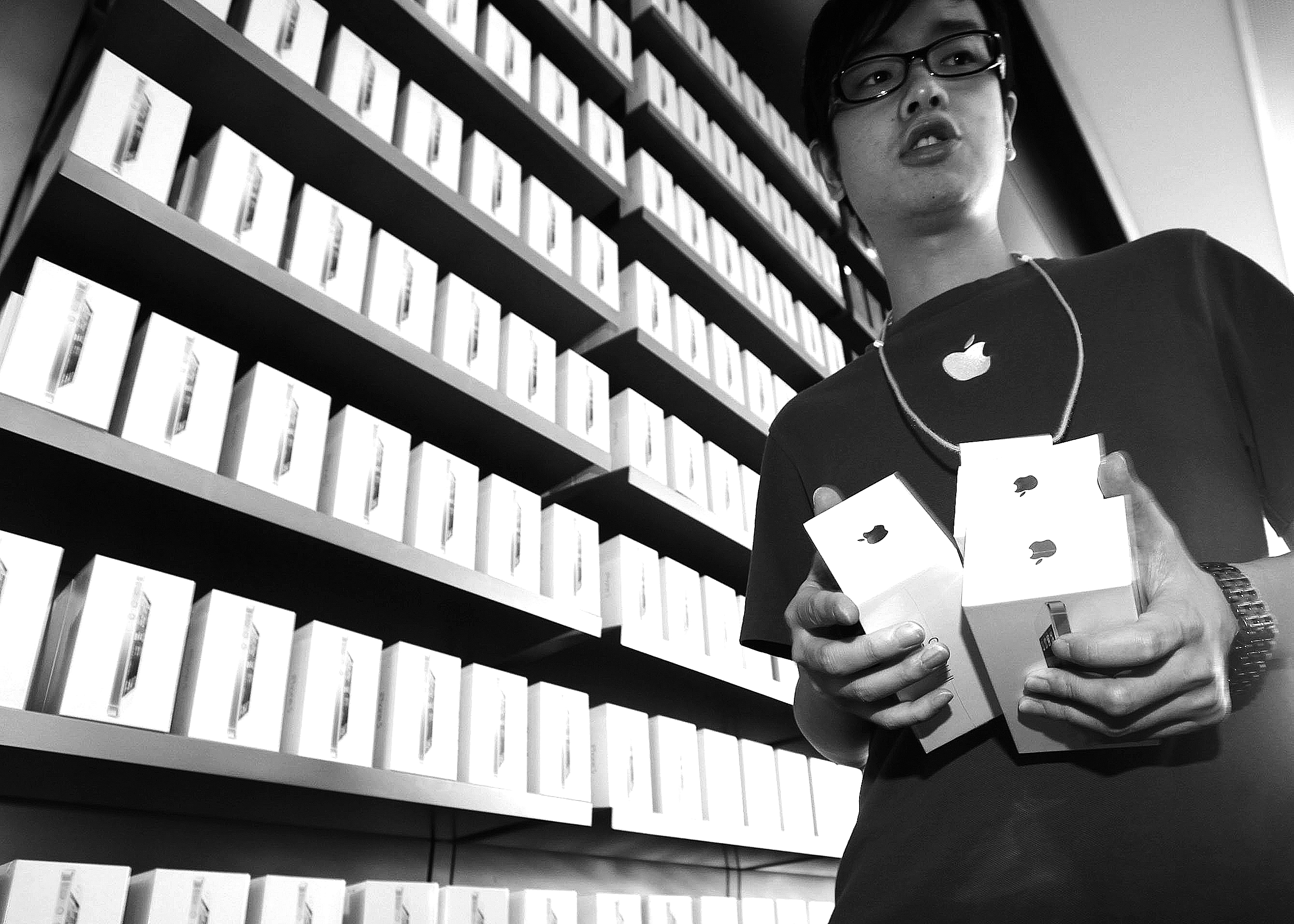 Apple store worker brings iPhone 5s to customers in Hong Kong as company prepares to expand its market by 22 countries this week. Friday, the phone debuted in the United States and eight other countries but exceeded last year's iPhone 4S launch by only a small margin.