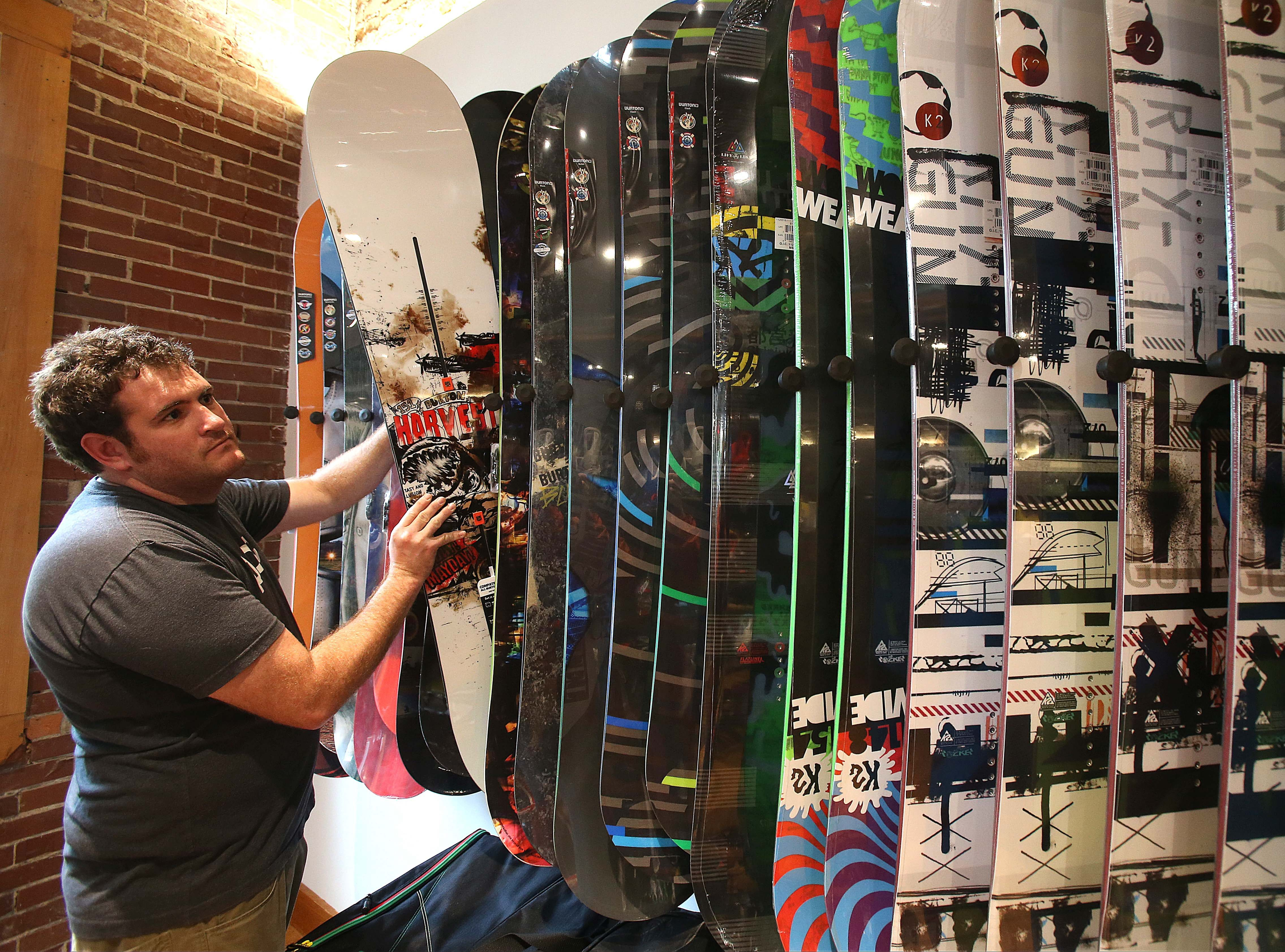 Robert Kirkham/Buffalo News  Nick Sciara, a boot fitter and salesman at Mud Sweat Gears in Ellicottville, arranges snowboards at the company's shop.