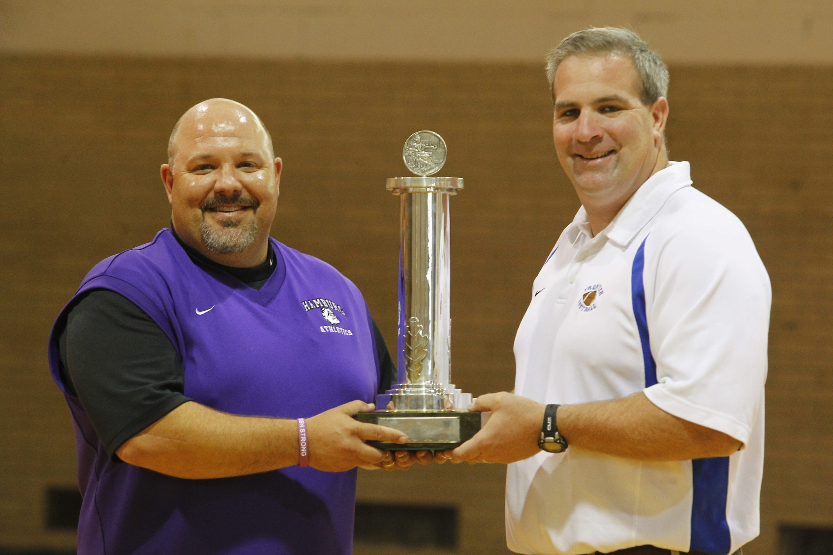 Mark Mulville/Buffalo News    Hamburg's athletic director, Greg Witman, left, and Frontier's athletic director, Rich Gray, hold the Challenge Trophy, which was used for years in a good-natured rivalry between the two school districts.