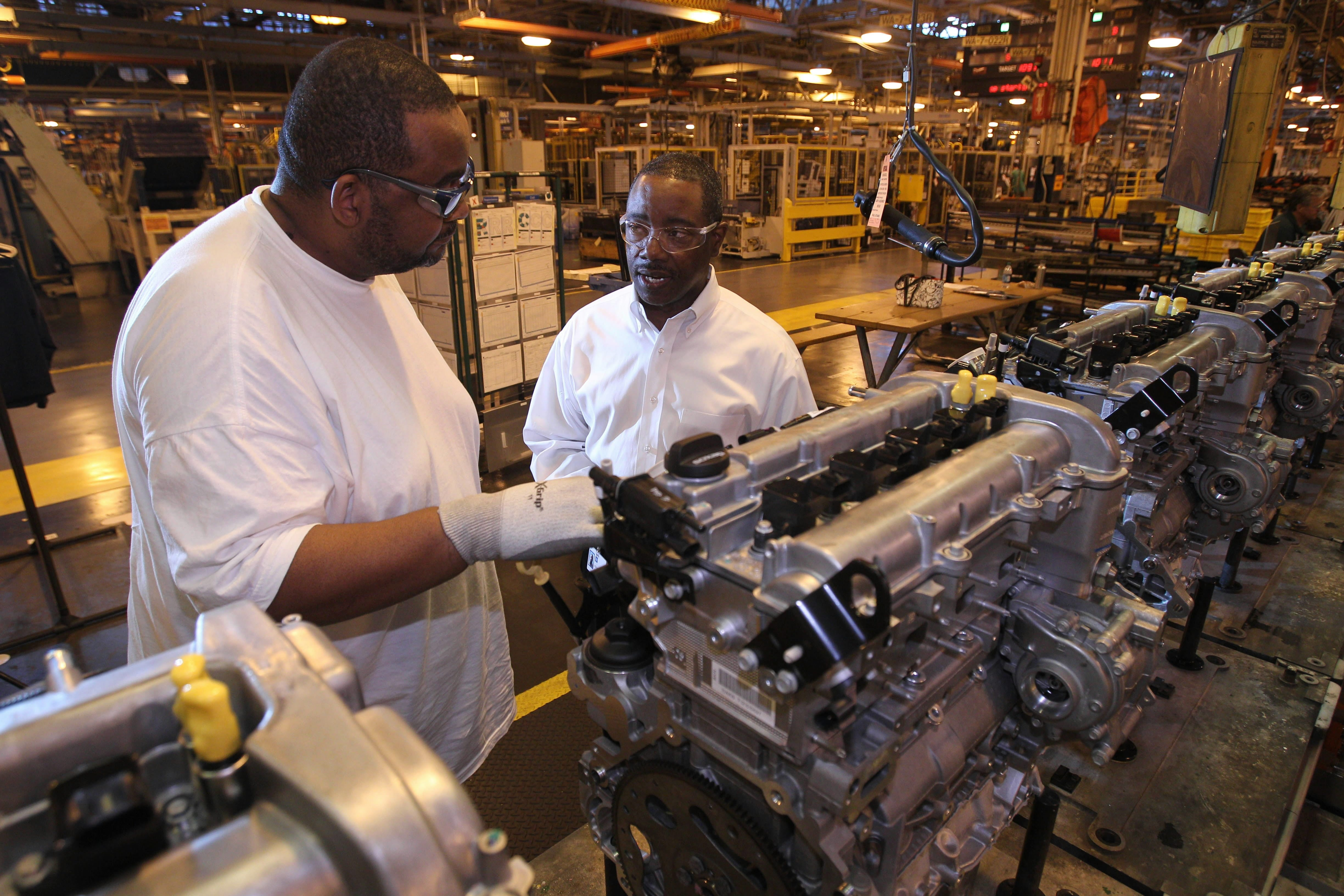 Steve Finch, right, plant manager, talks to engine technician Gregory Willoughby on the Ecotec 2.4-liter engine assembly line.  {Photo by Sharon Cantillon / Buffalo News}