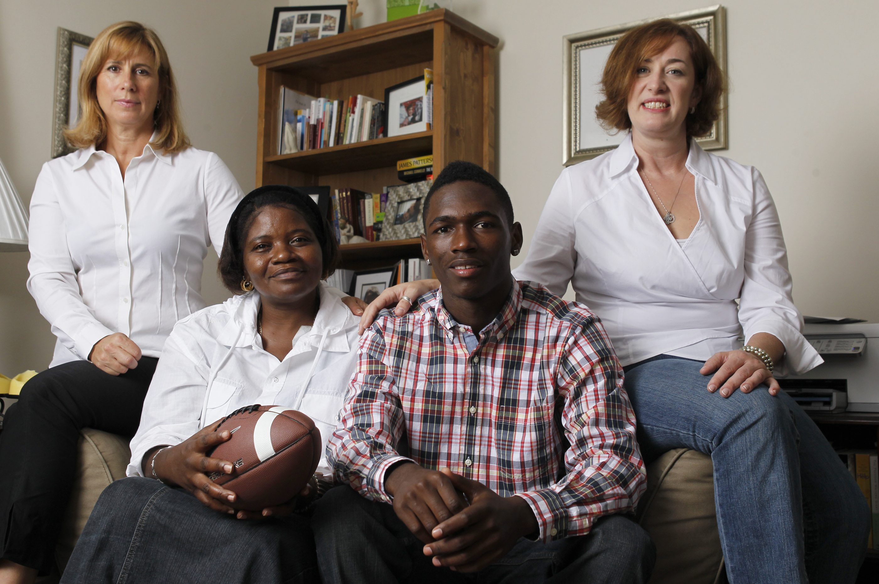 "Chaq Nettles, a Williamsville South student athlete, is pictured with his ""foster"" moms, Barbara Nuchereno, far left, and Heidi Rotella, far right, and his biological mother, Shirley Nettles, at the Rotella home on Saturday, Sept. 8, 2012. {Photo by Harry Scull Jr. / Buffalo News}"