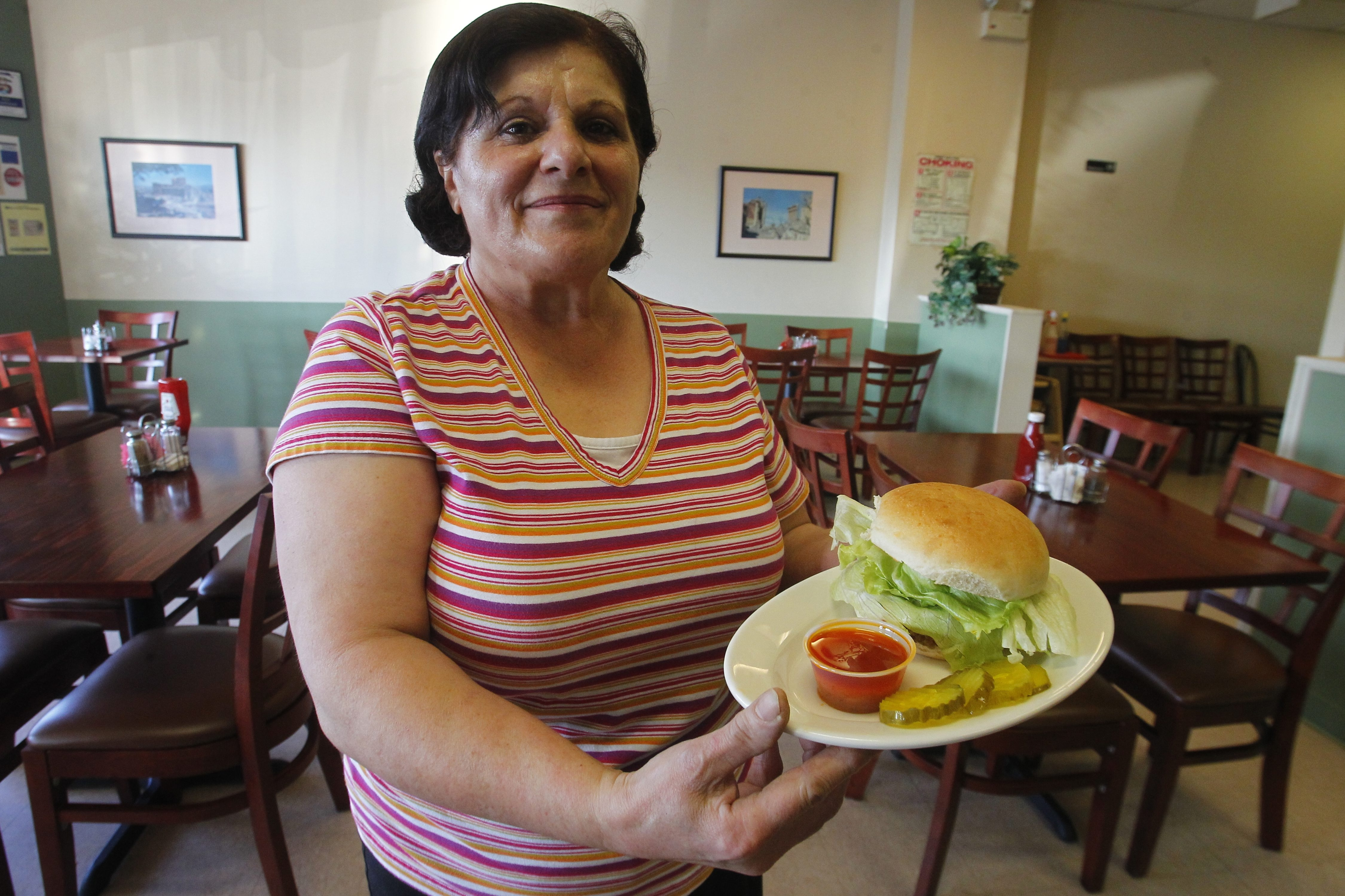 Cook Violette Mansour serves an eggplant tofu burger, one of four veggie burgers at Natalie's.