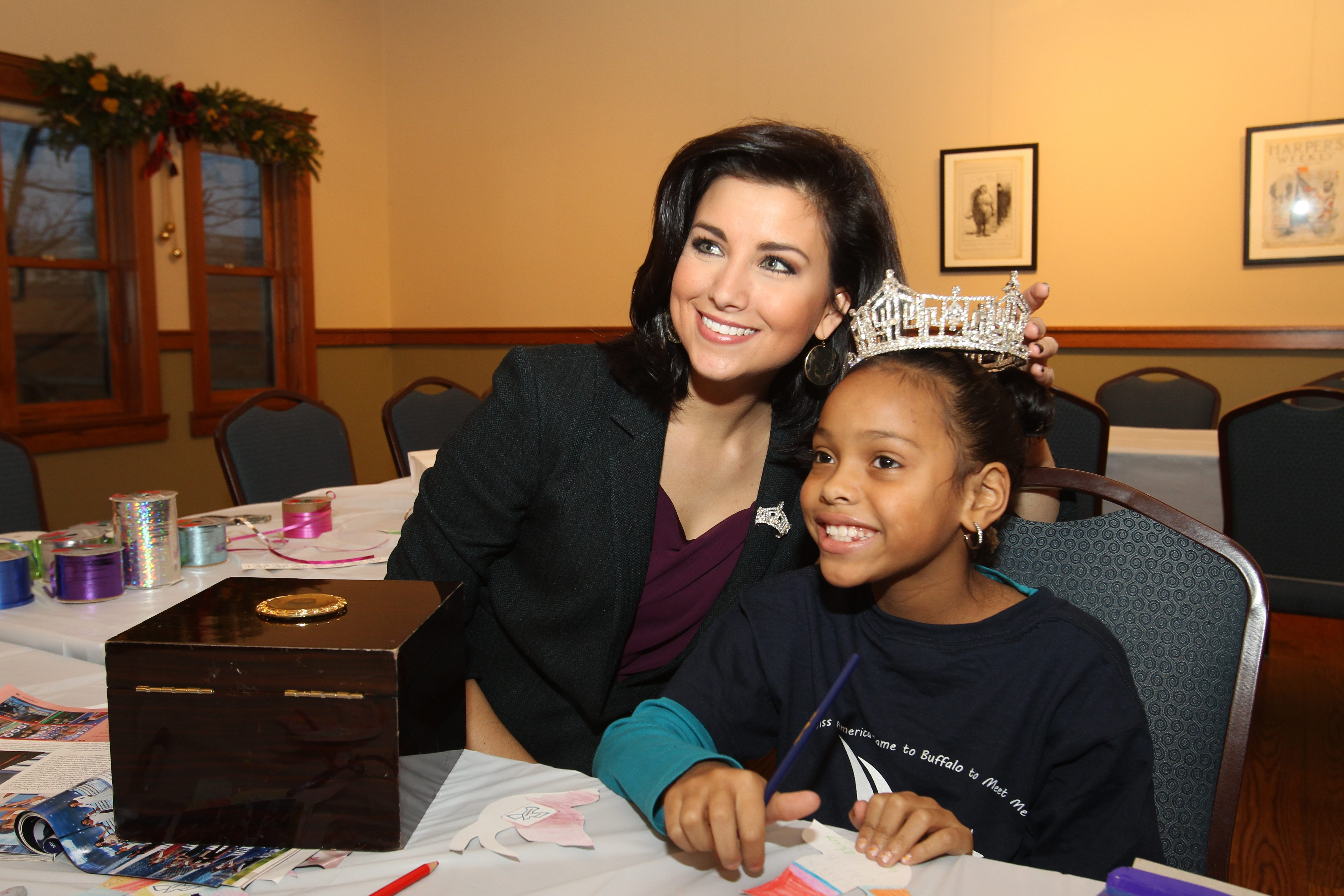 Miss America 2012 Laura Kaeppeler lets Na'ima Flores wear the coveted crown while the 7-year-old creates Christmas ornaments Wednesday at the Theodore Roosevelt Inaugural Historic Site.
