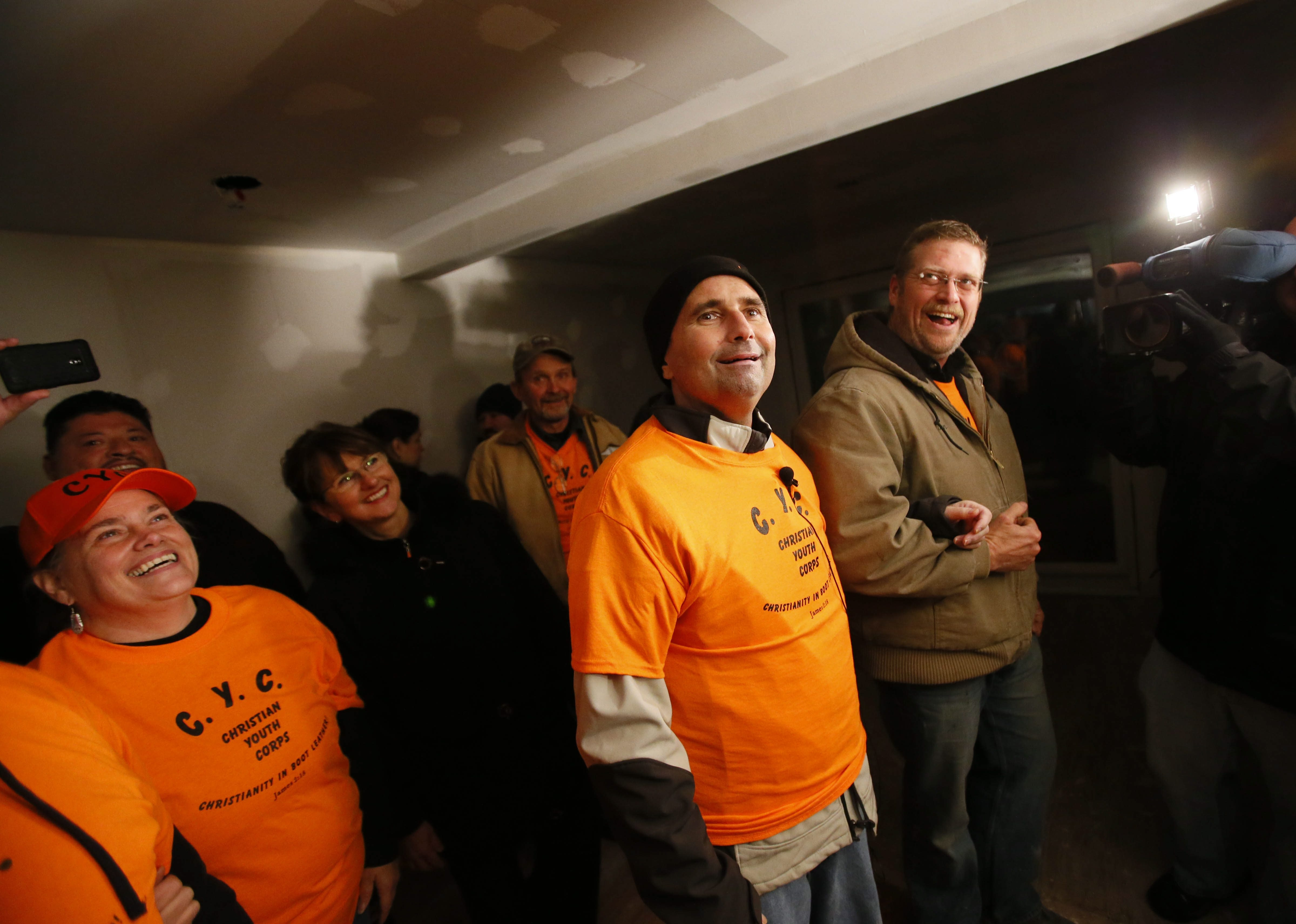 Norm Reformat, center, can hardly believe his eyes as he walks into his home after being released from ECMC on Tuesday. Dozens of volunteers have been renovating the home in Reformat's absence.