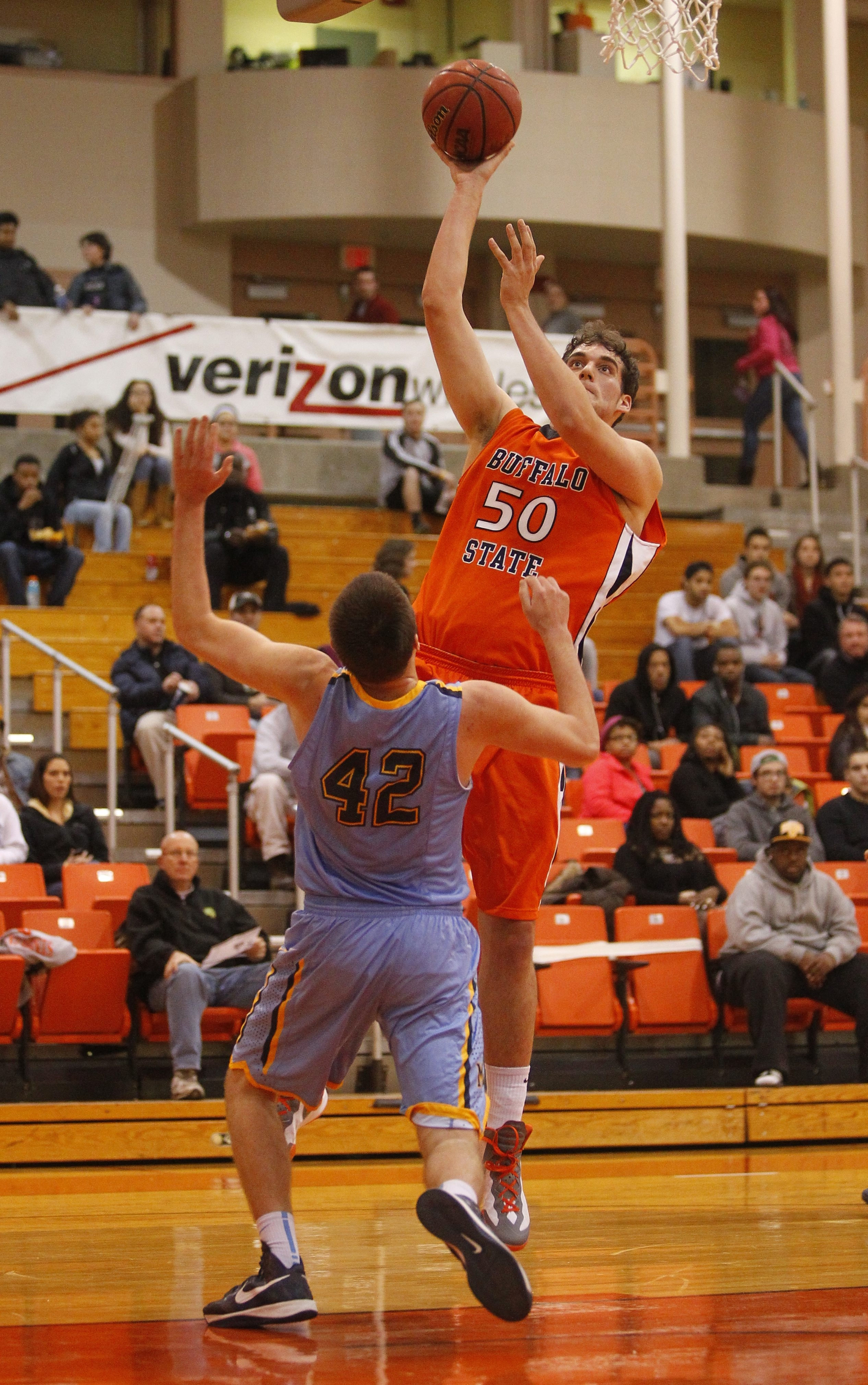 Buffalo State's Seth Runge (50) goes for a layup as  Medaille's Alex Baron (42) tries defend. {Photo by John Hickey / Buffalo News}