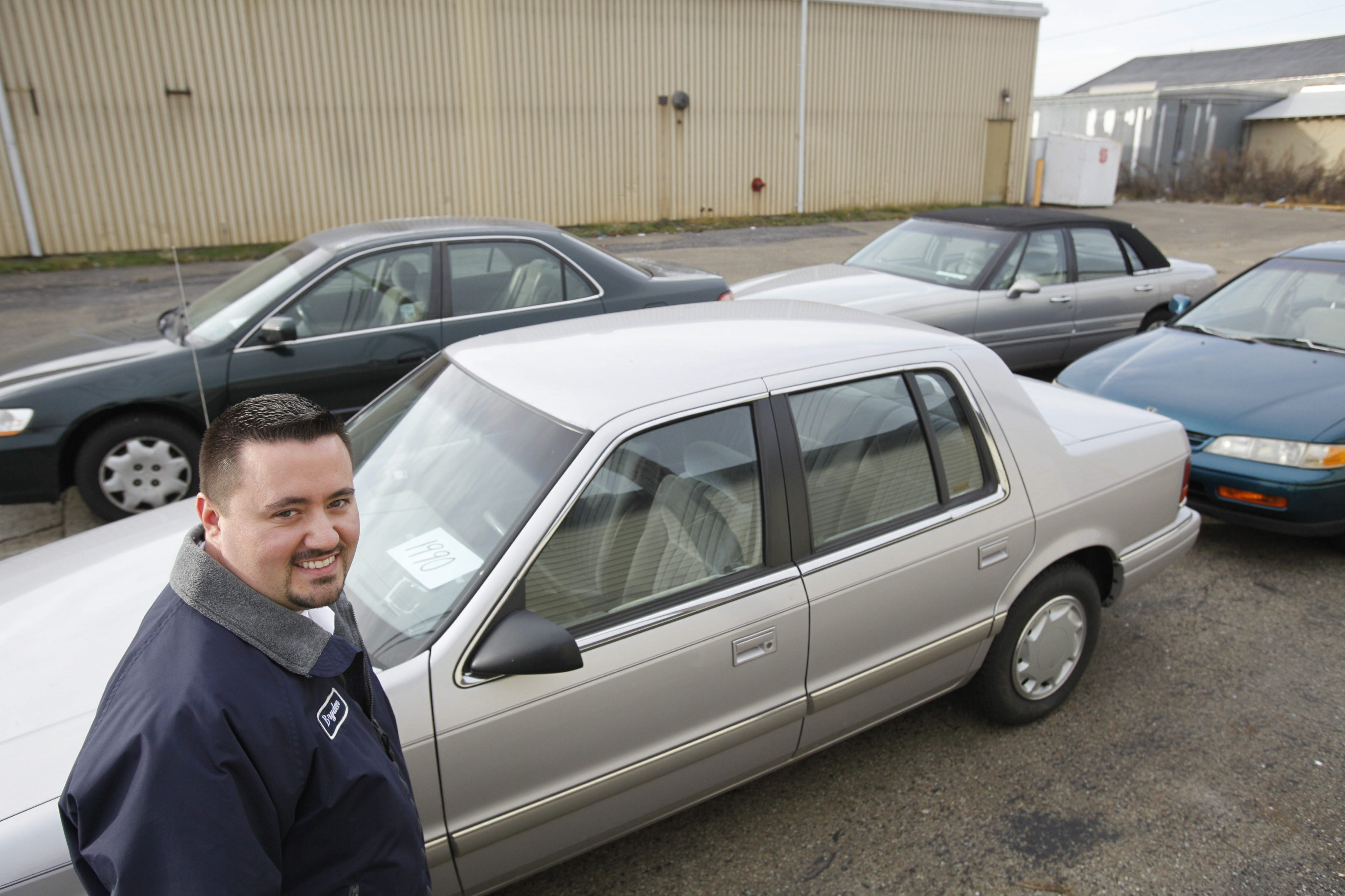 (Derek Gee/Buffalo News) Envoy Bryden Swires, administrator of the Salvation Army's Buffalo Adult Rehabilitation Center, with four automobiles that were donated to the agency that are sold in a silent auction, Tuesday, Nov. 20, 2012.