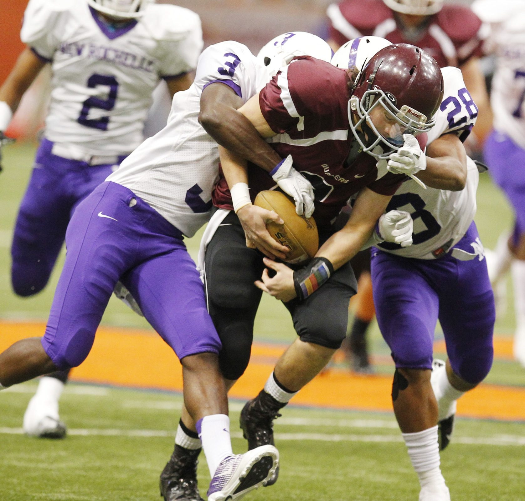 Orchard Park's Ben Holmes is tackled by New Rochelle's Shayne Forbes, right, and Jason Ceneus during Saturday's Class AA football championship.