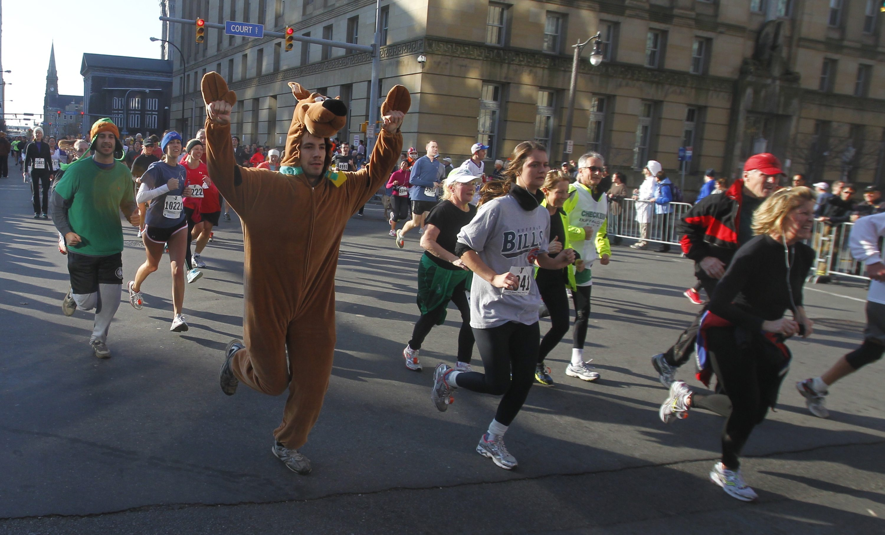 A runner dressed as Scooby-Doo nears the finish line at the Buffalo Niagara Convention Center. Turkey Trot organizers capitalized on participants' creativity by holding event's first costume contest beforehand.
