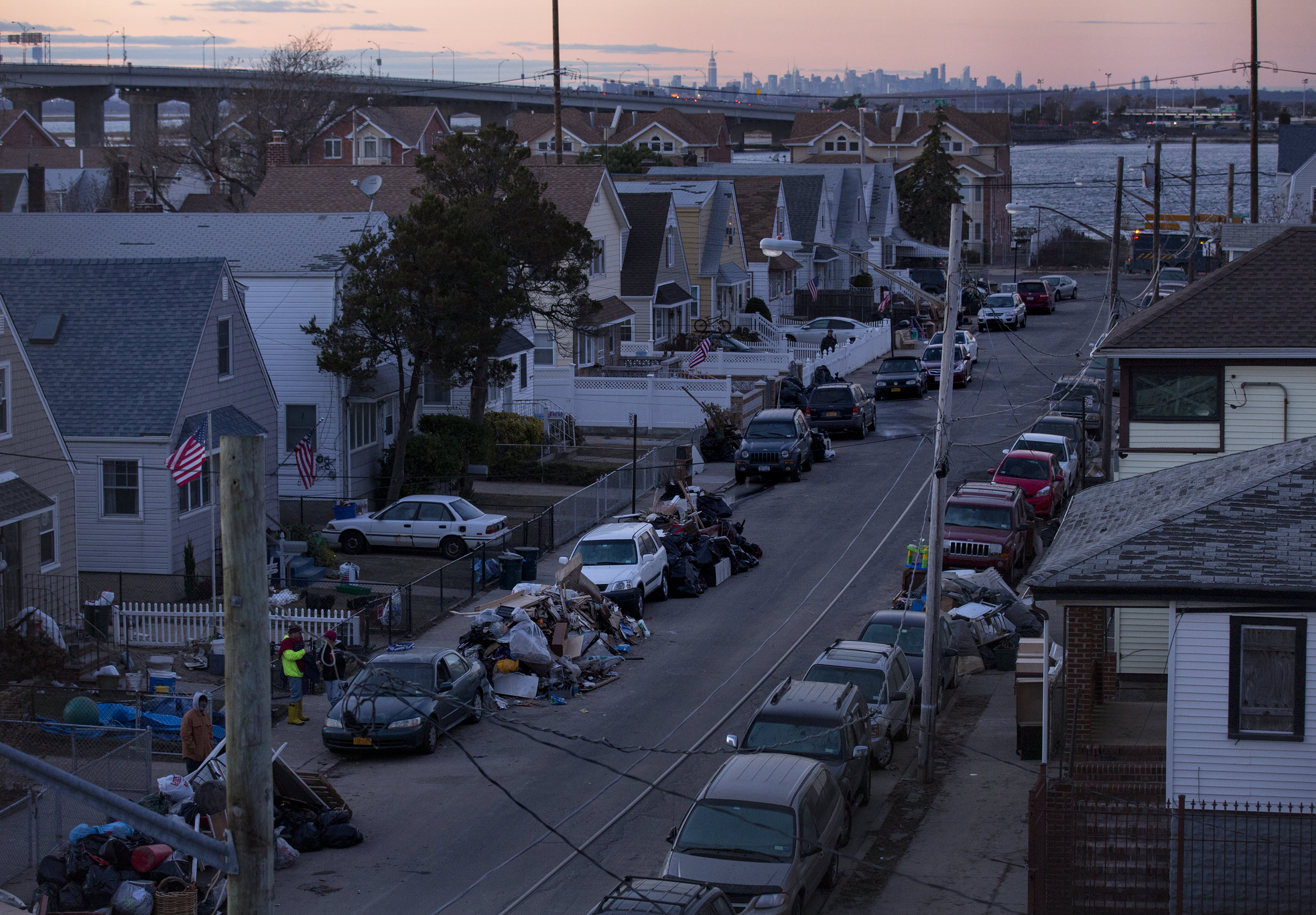 Debris lay in front of homes in a Rockaway neighborhood of the borough of Queens, New York, Monday, Nov. 5, 2012, in the wake of Superstorm Sandy. The Manhattan skyline is seen in the background. (AP Photo/Craig Ruttle)