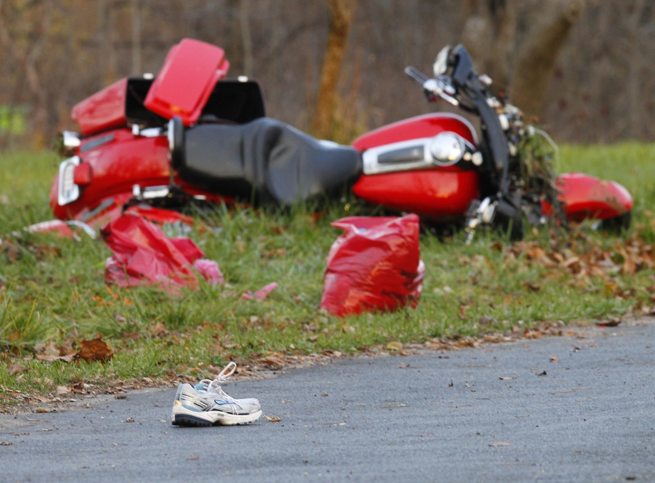 A motorcycle lies in the grass after the driver veered off the road and onto the bike path on Tonawanda Creek Road, killing two pedestrians and injuring a third on Sunday, Nov. 11, 2012.  The driver, David A. Smith, 53, of Niagara Falls was charged with driving while intoxicated and criminally negligent homicide.  (John Hickey/Buffalo News)