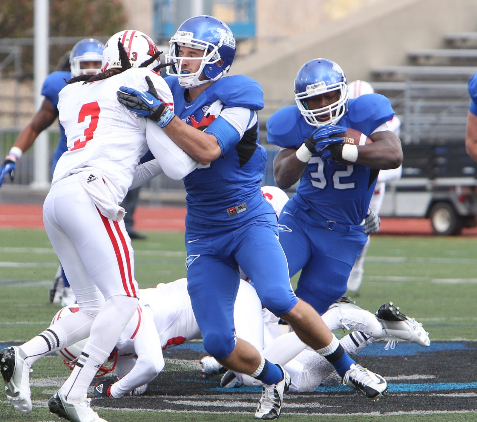 UB wide receiver Alex Neutz gives Branden Oliver (32) some running room as he blocks Miami's Dayonne Nunley (3) in the first half of the Bulls' victory.