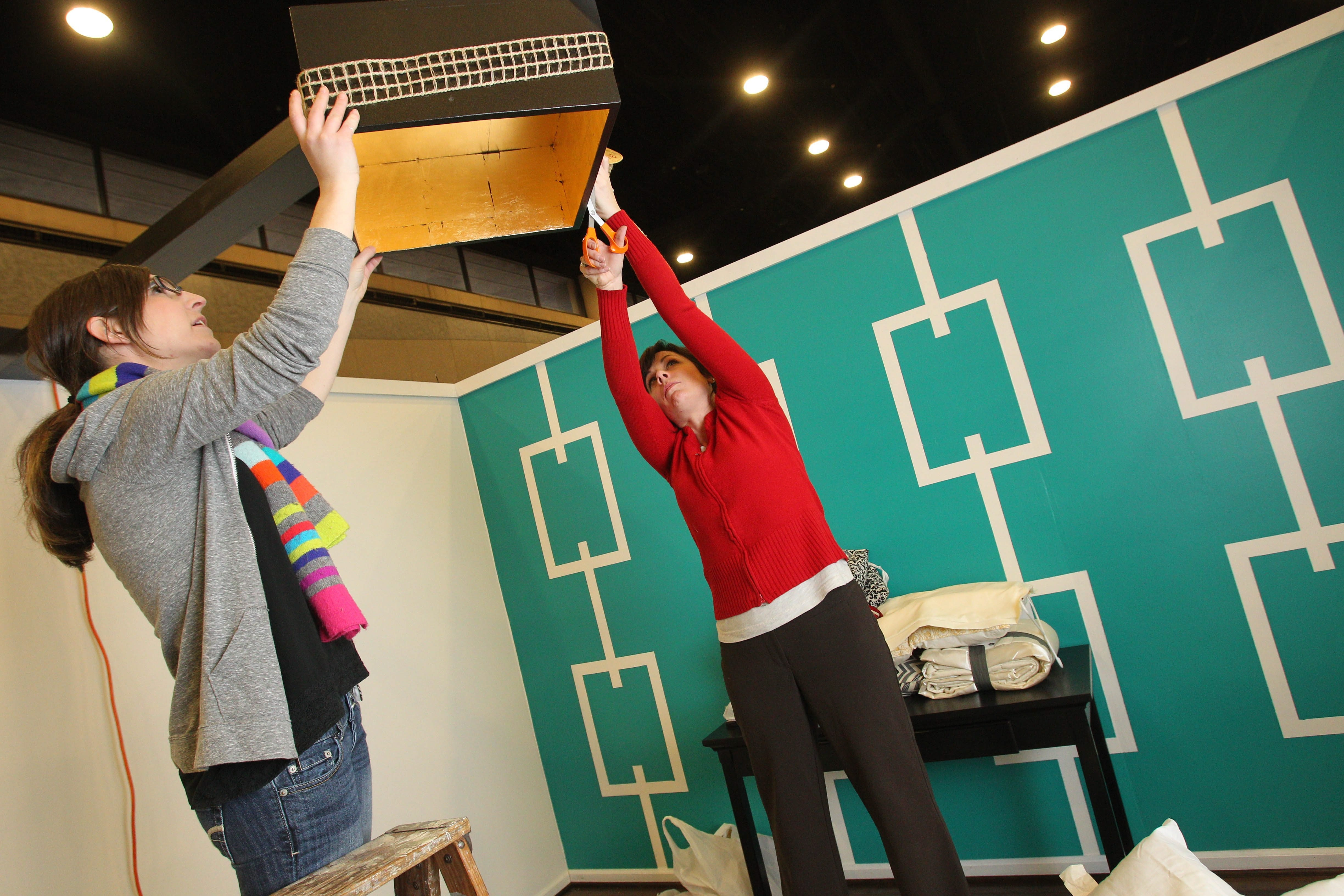 This year's feature at the Buffalo Home and Garden Show at the Buffalo Convention Center is called the 'White Room Challenge.  Heather Benson, left, and Nicole Milley, partners of Nikki M. Design in Buffalo create a modern eclectic bedroom.  They are working on the light fixture which is using the cube, one of the elements given to the designers to incorporate into the room.  (Sharon Cantillon/Buffalo News)