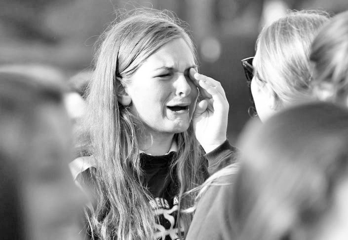 Erin McCormick, a junior at Holy Angels Academy, cries after learning the news that the 152-year-old school, which has 240 students in grades 6 to 12, will close in June.