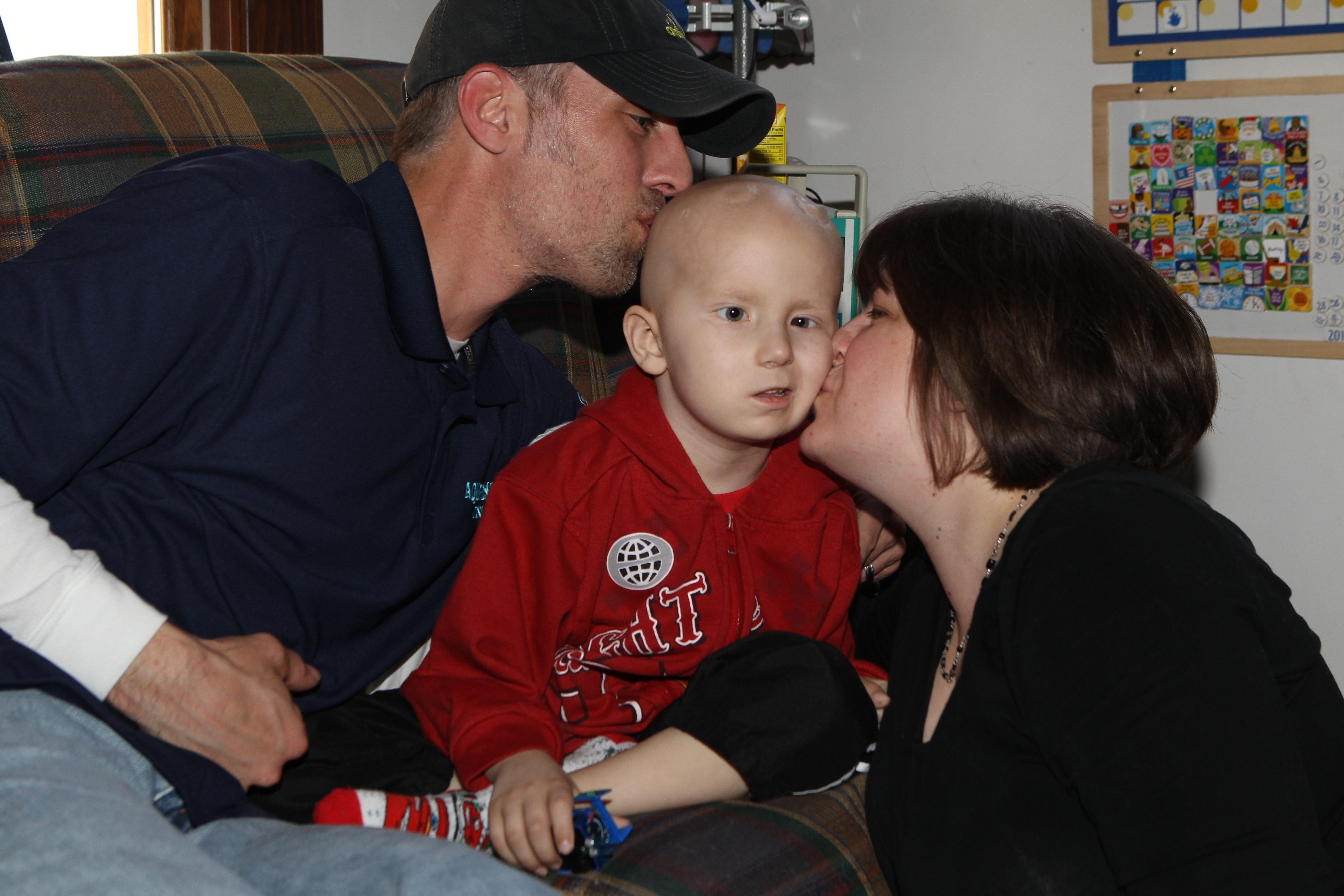 Tom and Jill Bojarski share a kiss with their son Jackson at their West Seneca home. The family is hoping Jackson will be well enough to travel to California next year for a special visit to Cars Land.