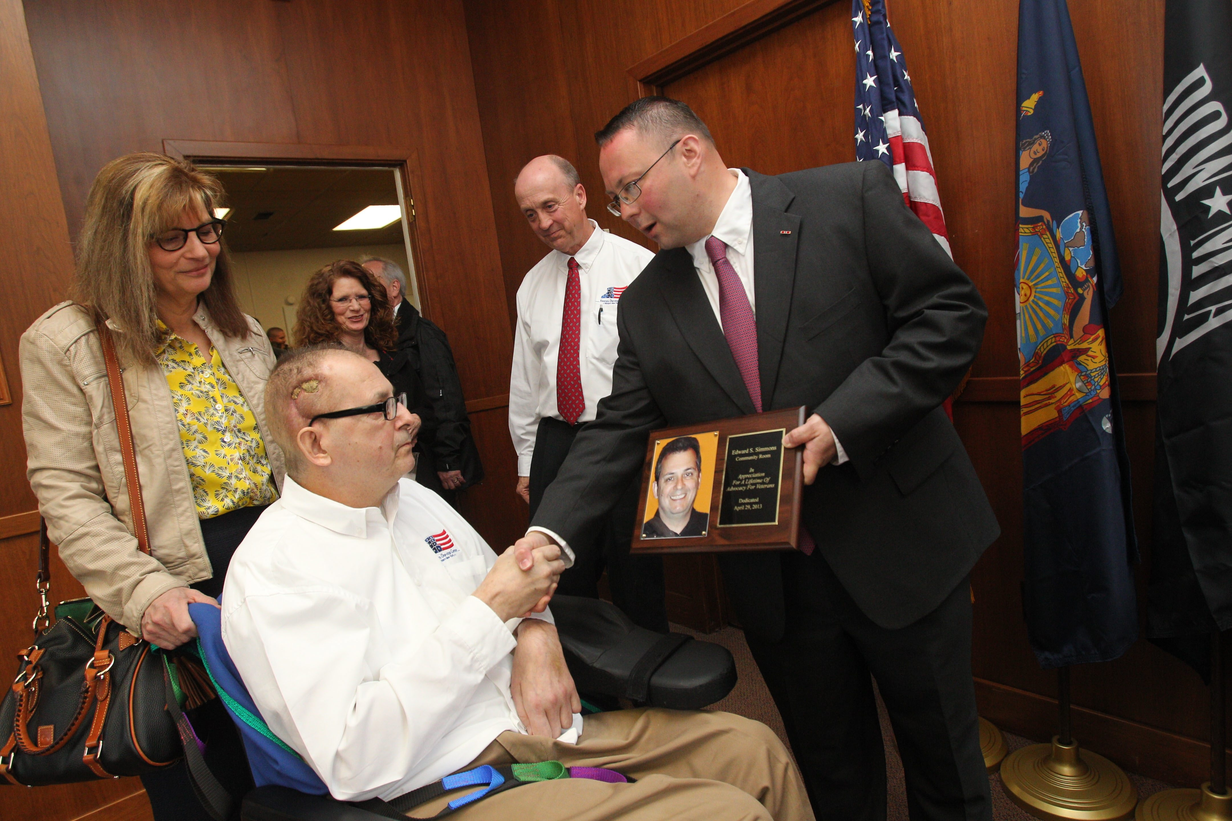 Roger L. Woodworth, right, president and CEO of the Veterans One-stop Center, shows a plaque to Edward Simmons, center, at the center Monday. Simmons' wife, Onda, left, and Harry Schultz look on.