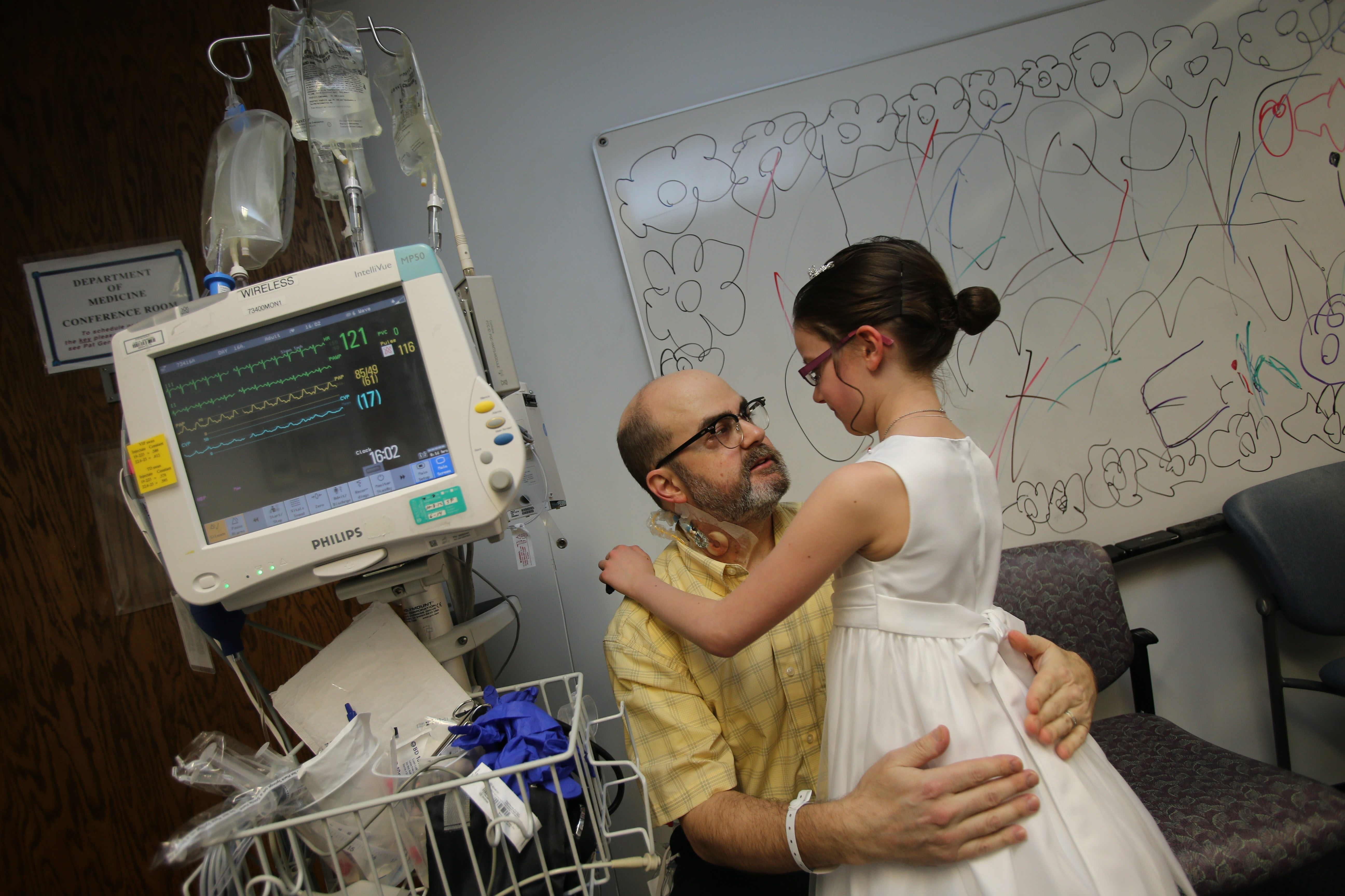 Erin Day gets a hug from her father, Tim, while preparing for a First Communion ceremony in Strong Memorial Hospital, Rochester.
