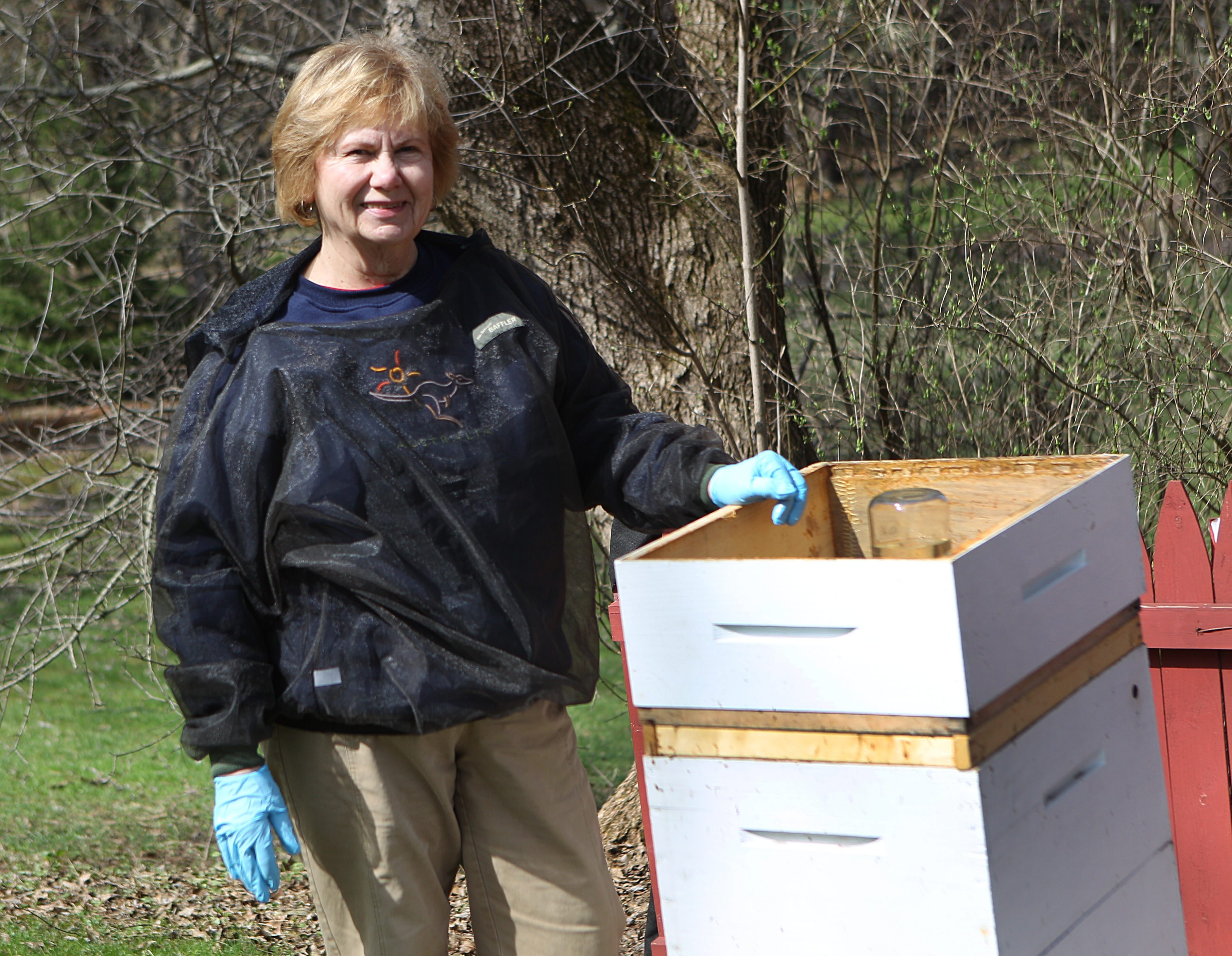 """Barbara Ochterski of East Aurora tends to one of her beehives. She says honey is """"pure, unadulterated food."""""""