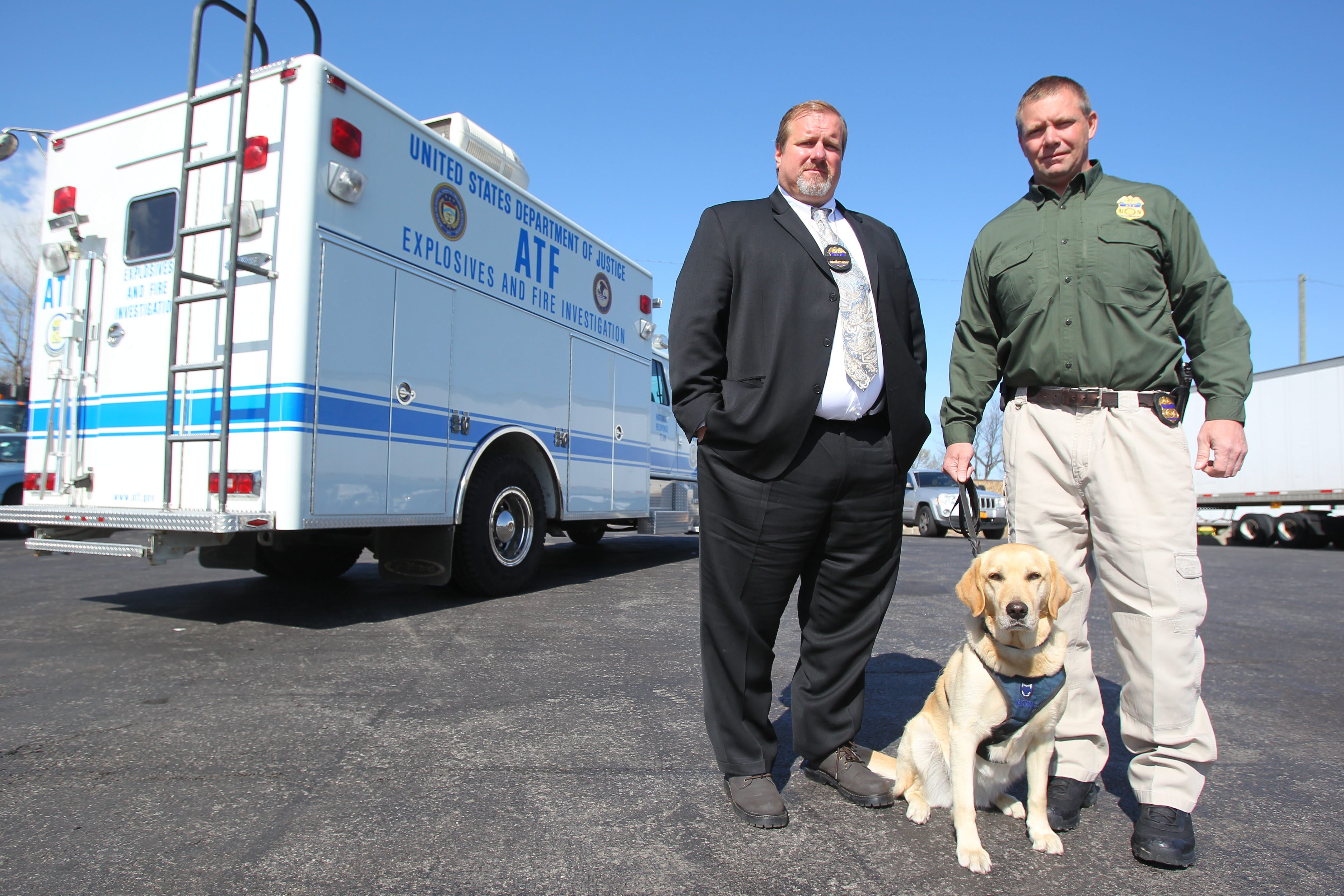 Bureau of Alcohol, Tobacco, Firearms and Explosives special agent Gerry O'Sullivan, right, and Dolly, an explosives detection canine, are joined by fellow ATF special agent Steve Dickey.