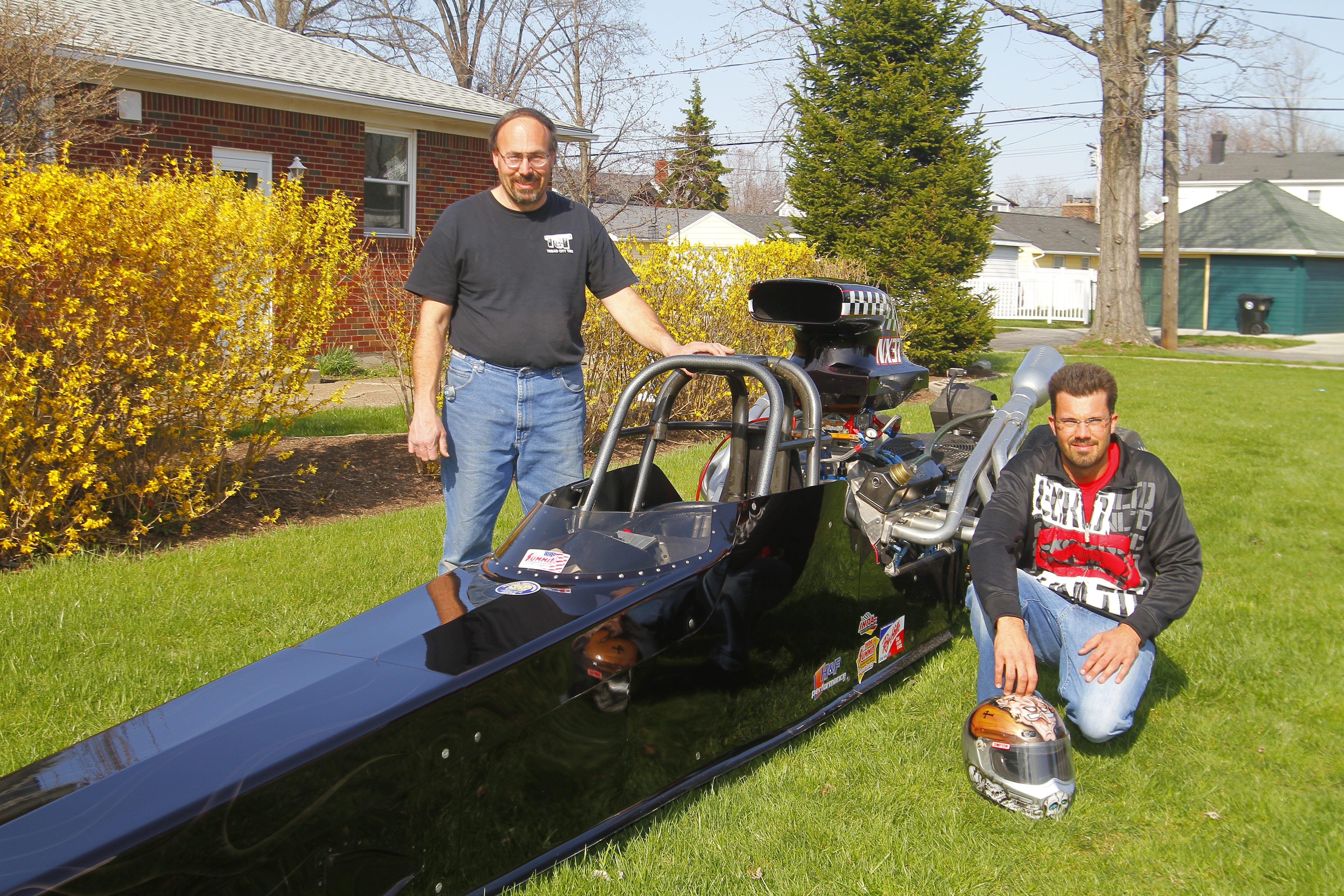 Pete Maduri Jr., right,  and his father Paul Maduri Sr. show off one of the two cars the younger Maduri will use during a racing season in which he will test his skills by participating in regional and national events in addition to local races in Lancaster.
