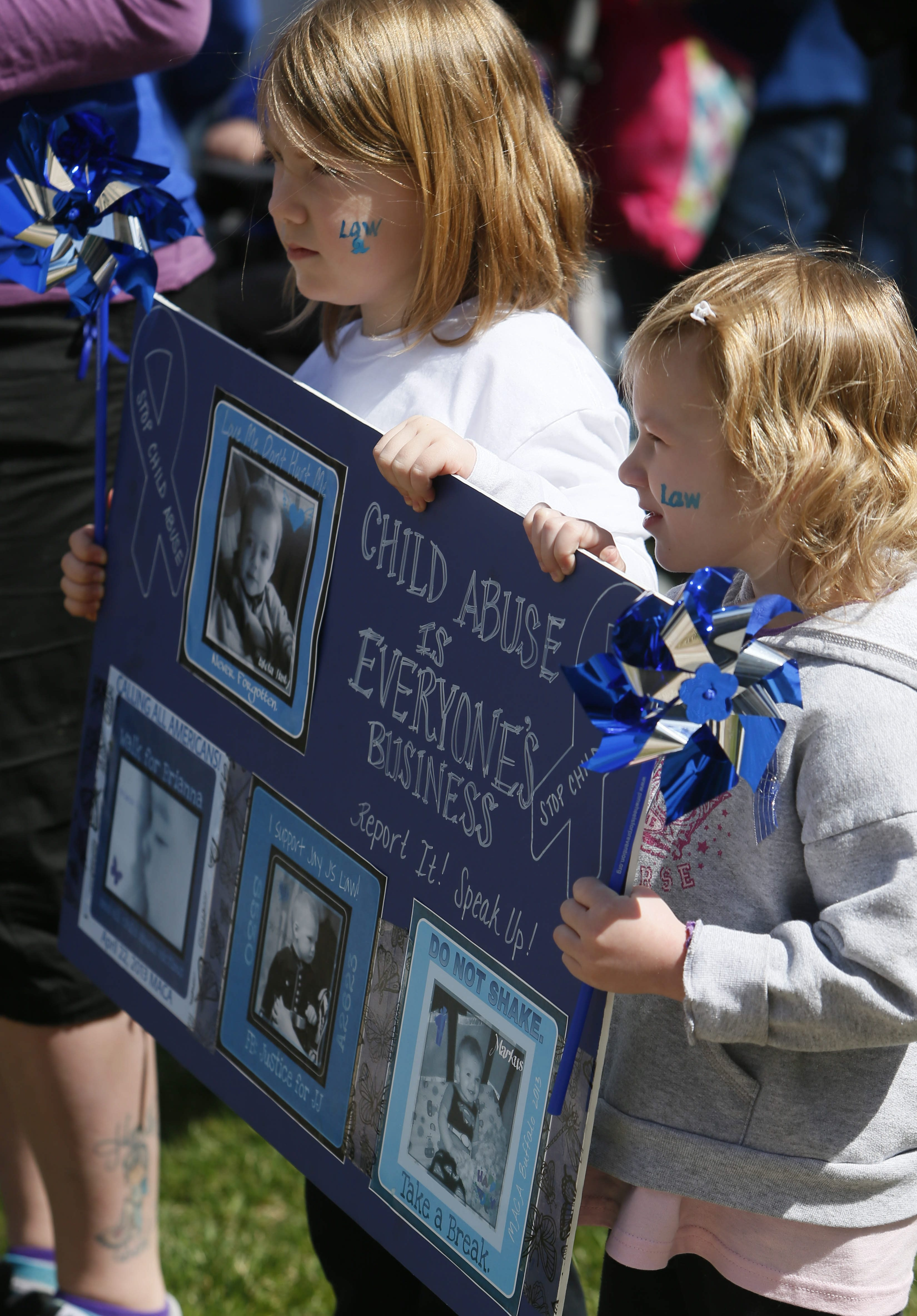 """Cianna and Ava Herrera, ages 5 and 4, send message that issue of child abuse is """"everyone's business"""" as their sign captures spirit  of Monday's march by about 250 advocates."""