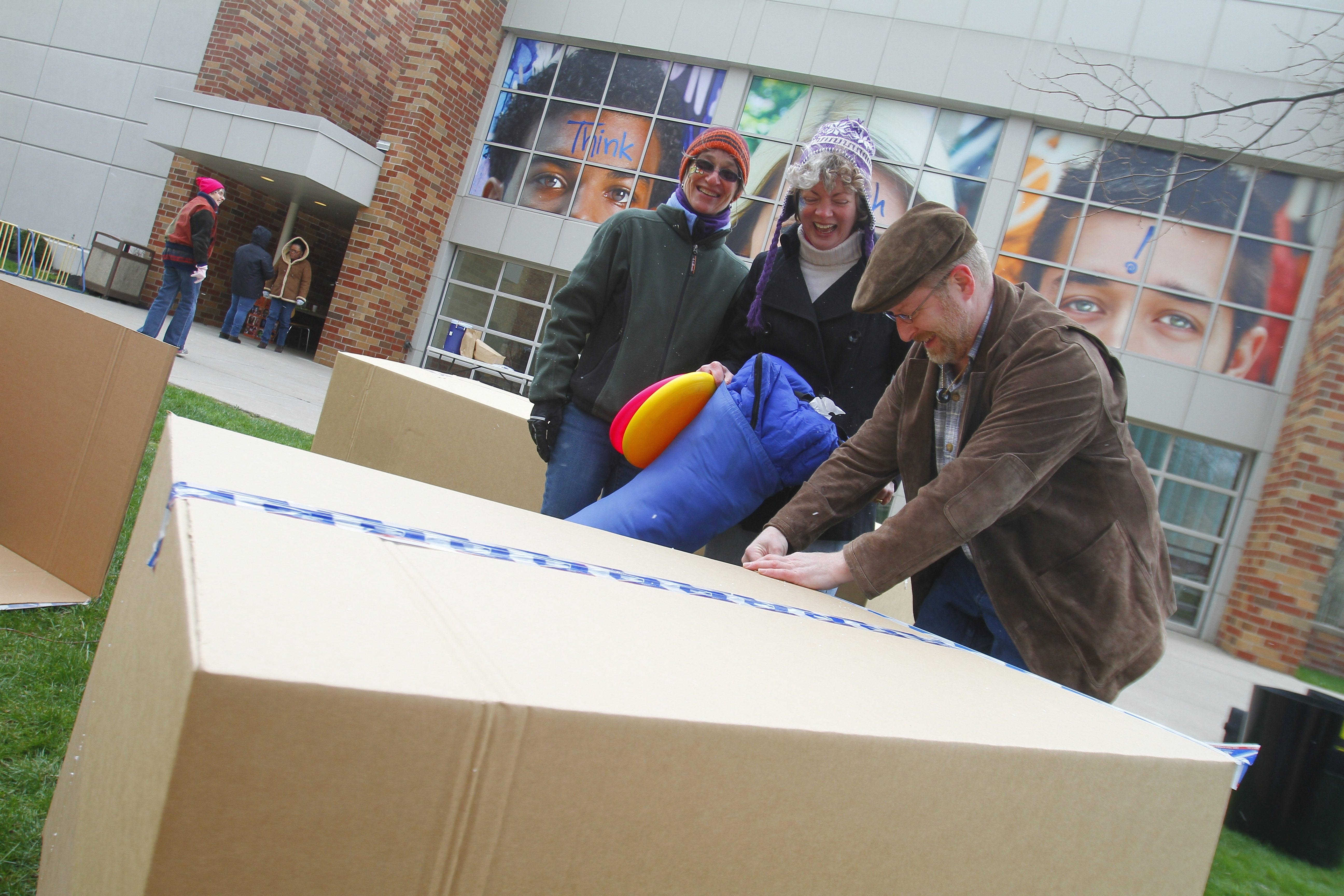 """Marilyn Sozanski, left, and Laura Genco of Family Promise, center, watch as Laura's brother-in-law, Charlie Genco, tapes up boxes Saturday at the fundraiser in """"Cardboard Box City"""" in Buffalo."""