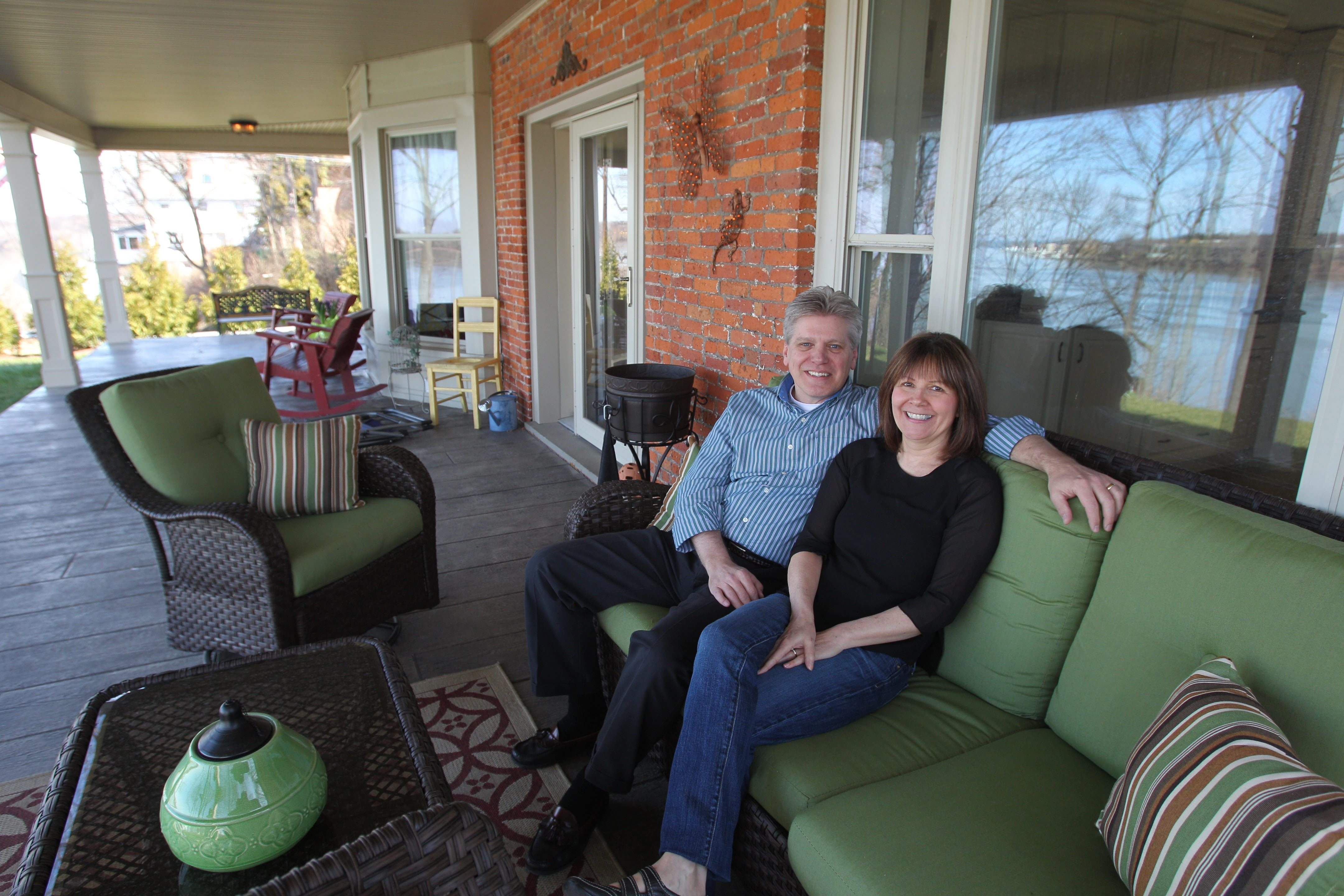 Greg and Kathy Schlaich show off their 19th Century gem on the NIagara River in Youngstown, Monday, April 15, 2013. Here, they're ion their wraparound porch overlooking the river.  (Sharon Cantillon/Buffalo News)