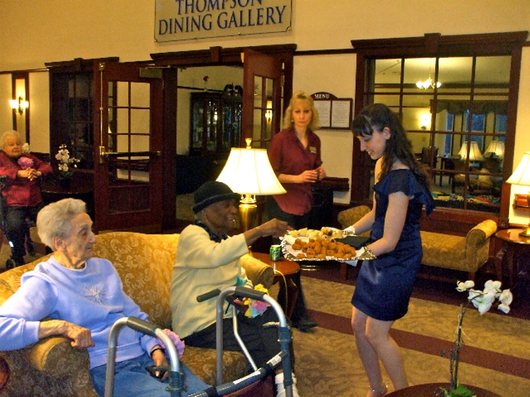 """Kelci Schlierf serves hors d'oeuvres to Barb Hudson, in back, Kay Fronczak, front left, and Mamie Warren at the """"Senior's Prom"""" at Brompton Heights in Williamsville, while staff member Linda O'Brien stands by to help out. Beverly Carnrike, inset, attended the prom, too."""