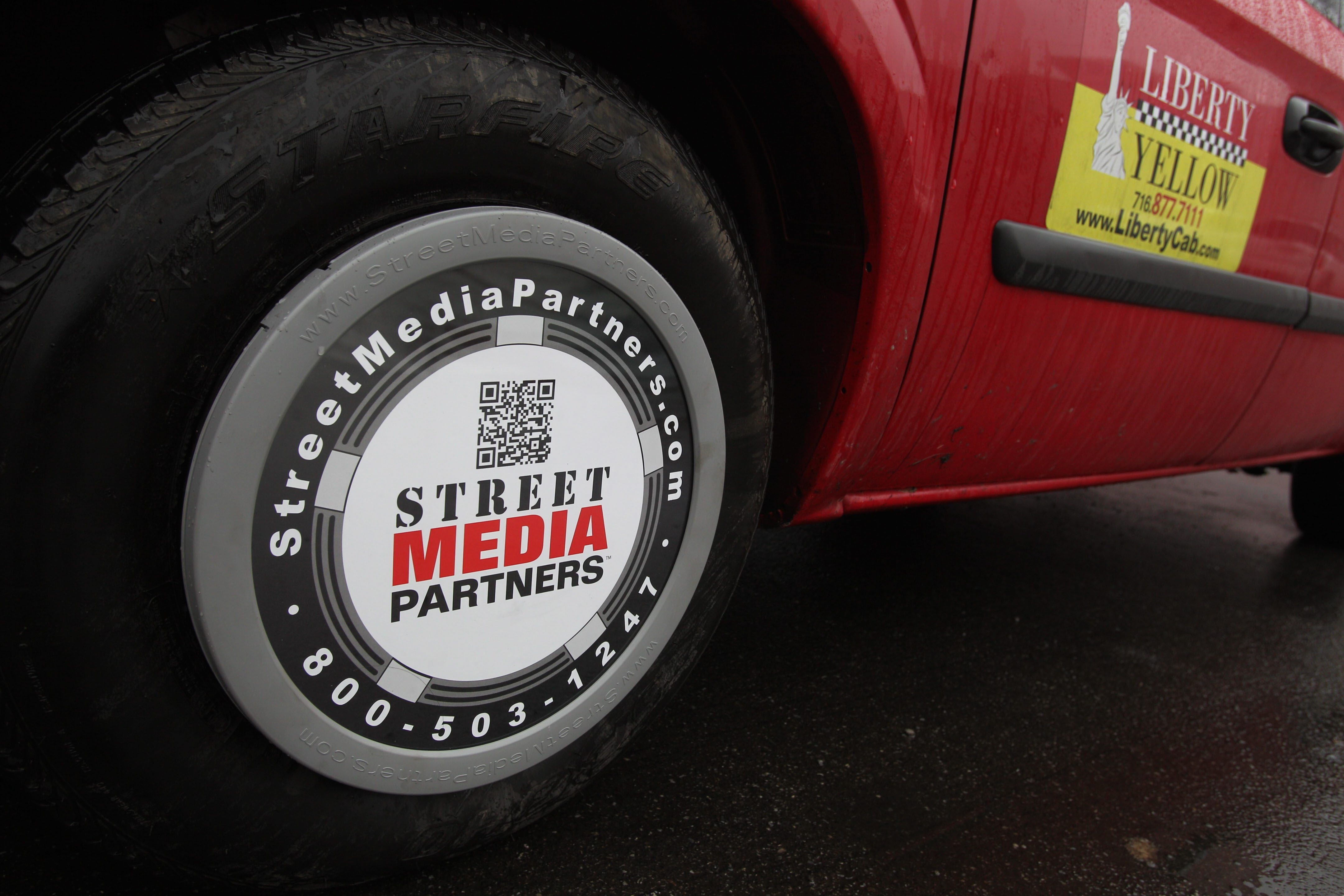 Street Media Partners designed a type of advertising that goes on taxicab hubcaps and glows at night. Buffalo's Liberty Cab will give the technology a trial.
