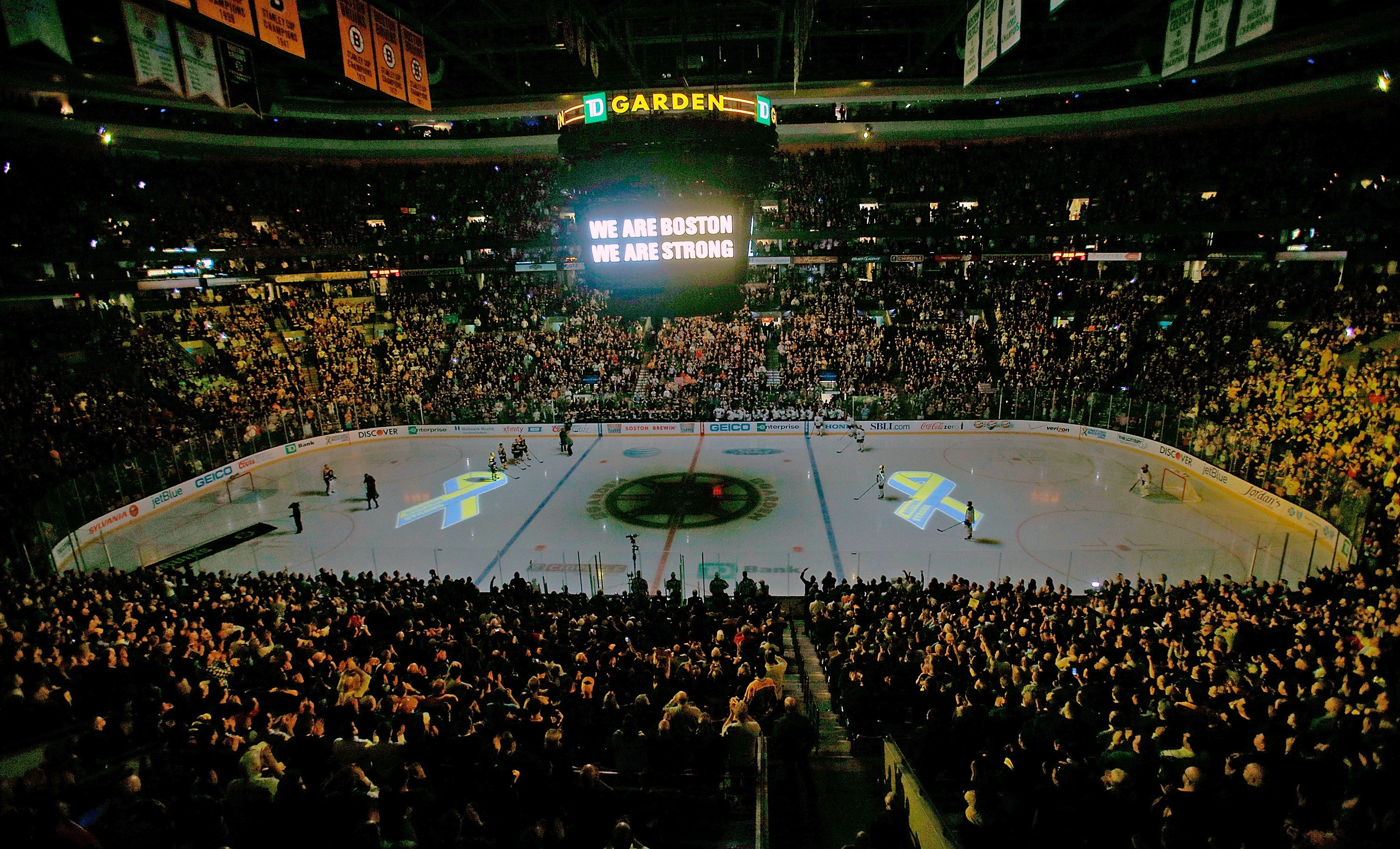 Projected images of the Boston Marathon Memorial Ribbon are seen on the ice during pregame ceremonies in remembrance of the bombing victims before Wednesday's game between the Sabres and the Bruins.