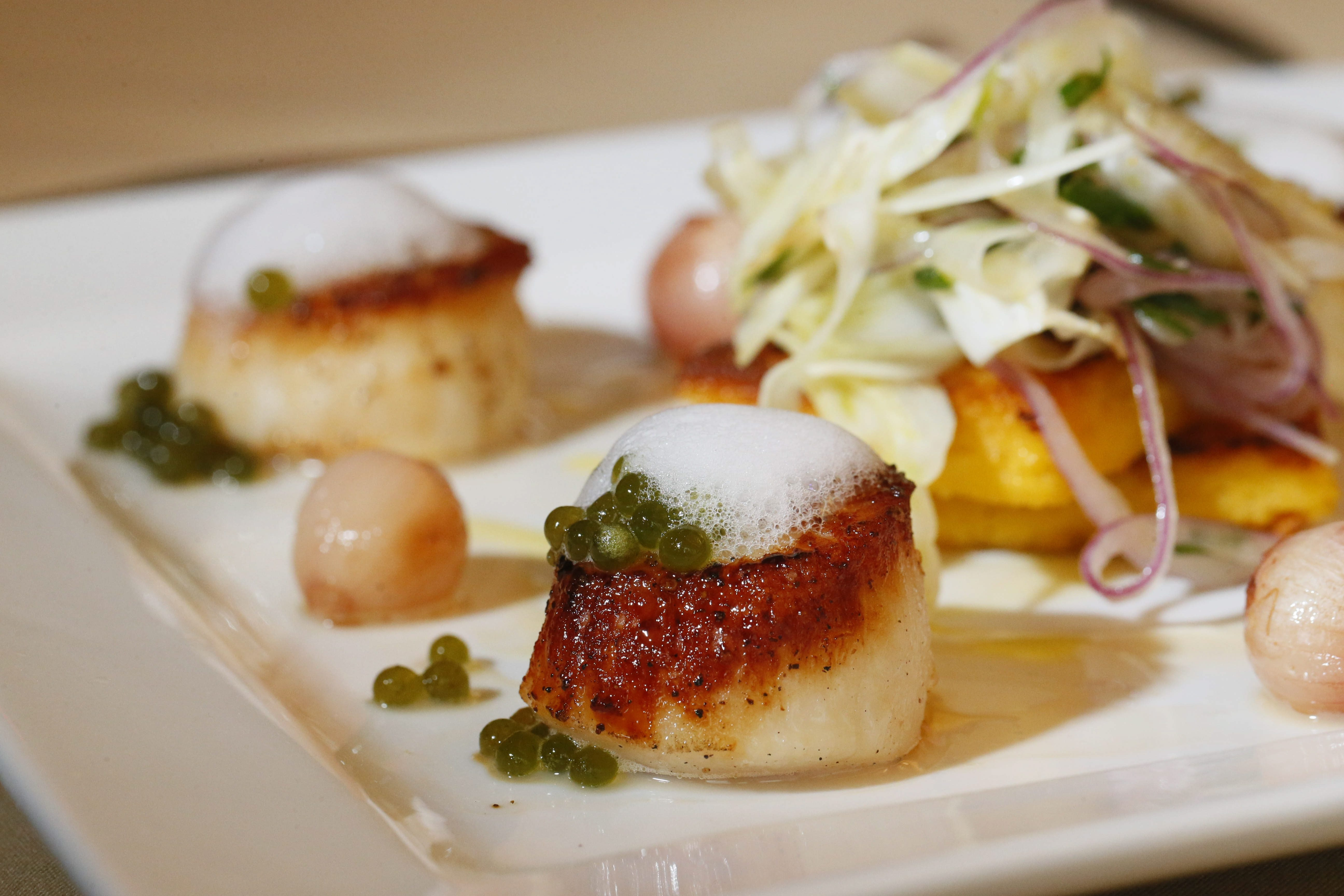 Scallops, topped with lemon-thyme foam and basil pearls, served with polenta, fennel salad and beurre blanc at Savor, the restaurant in the Niagara Culinary Institute in Niagara Falls.  (Derek Gee/Buffalo News)