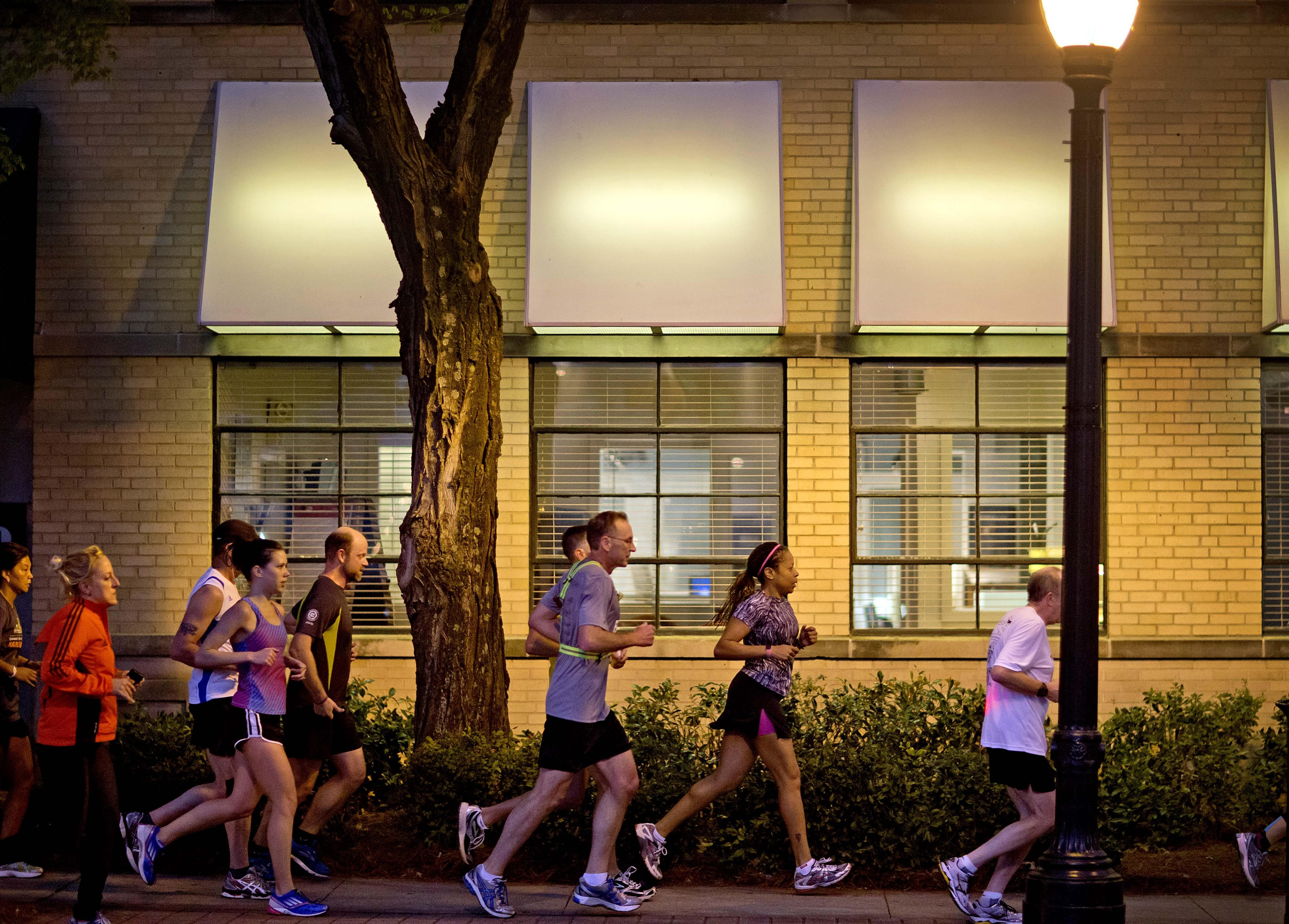Runners jog along Peachtree Street in Atlanta on Tuesday as part of an organized moment of silence and a memorial run to show solidarity with the victims of the Boston Marathon bombings.