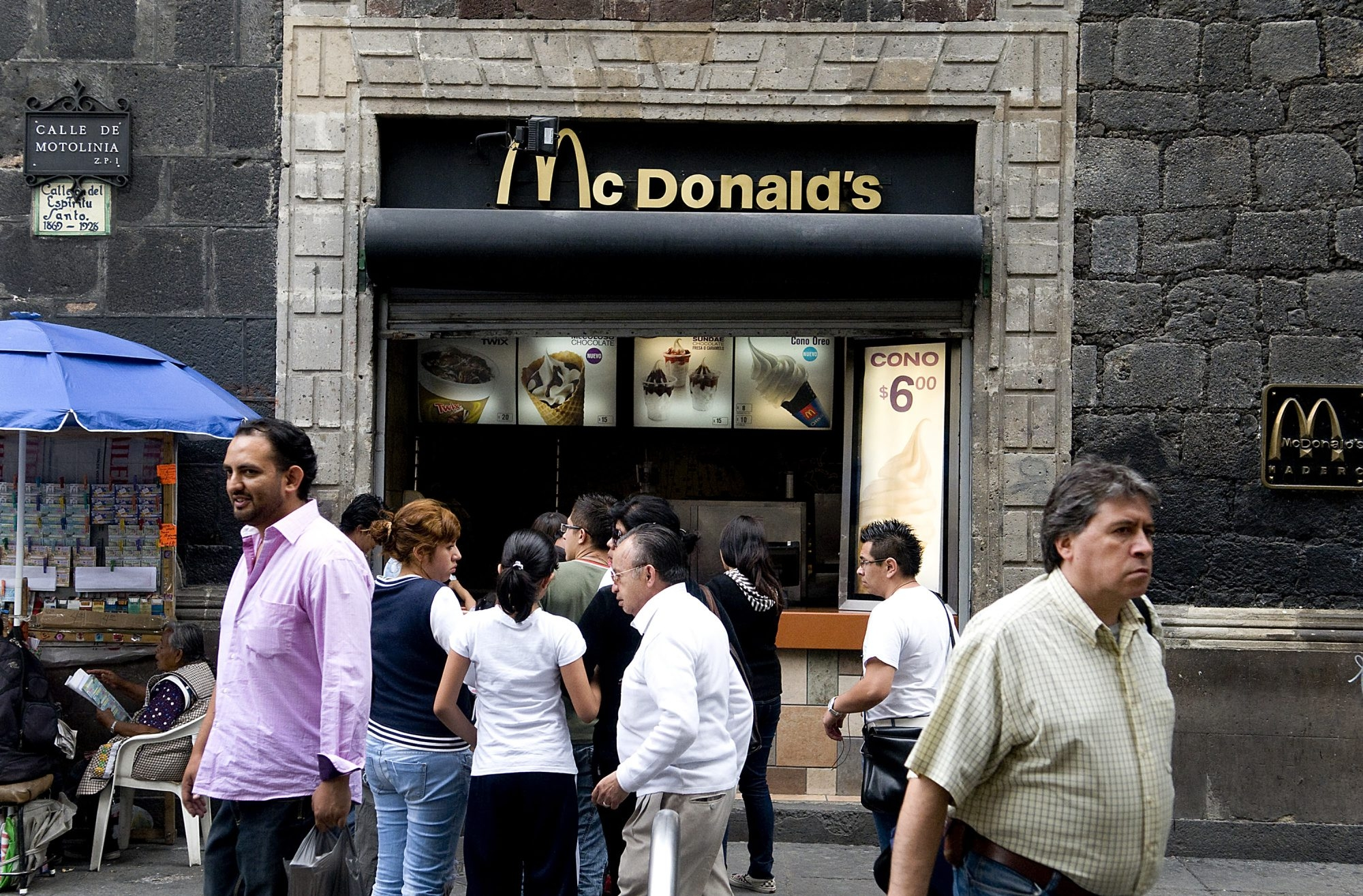 Pedestrians pass in front of a McDonald's restaurant in Mexico City, Mexico. Fast food restaurants have expanded around the globe, and residents' waistlines have expanded as well.
