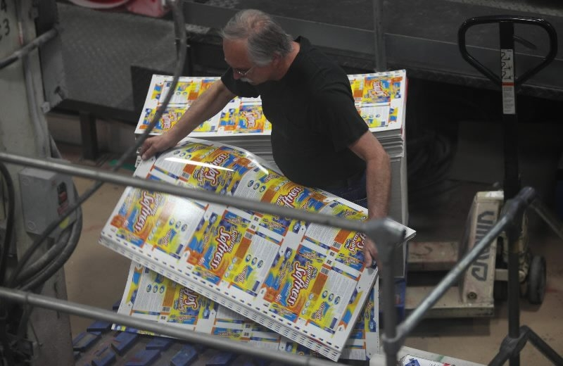 An employee picks up stacks of printed sheets at specialty printing firm Mod-Pac.   (Buffalo News file photo)