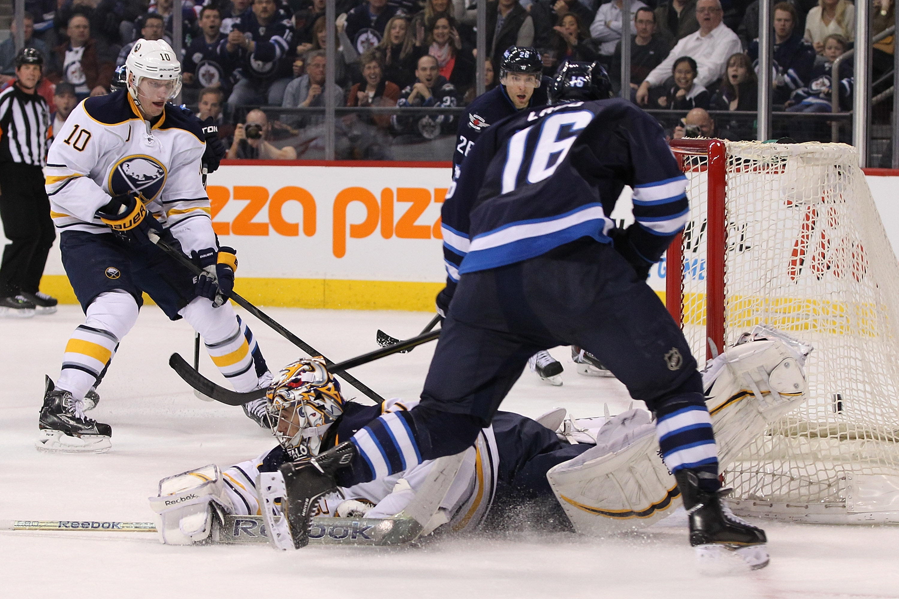 Goaltender Ryan Miller of the Sabres sprawls on the ice as Winnipeg's Andrew Ladd (16) scores in the second period.