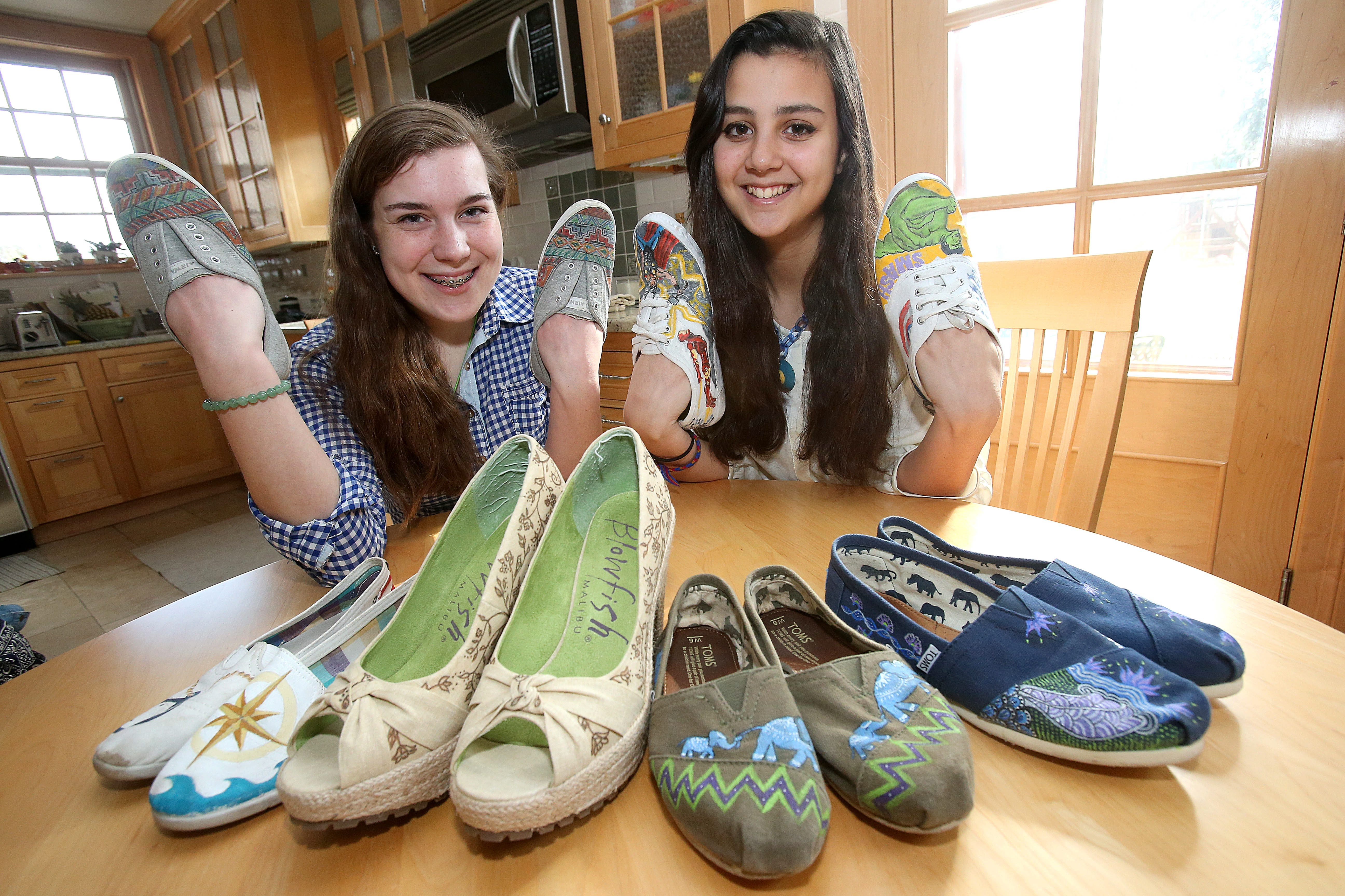 Nardin sophomore Clare Galbo, left, with friend and helper Annie Schenk, shows off some of the shoes she has painted designs on.