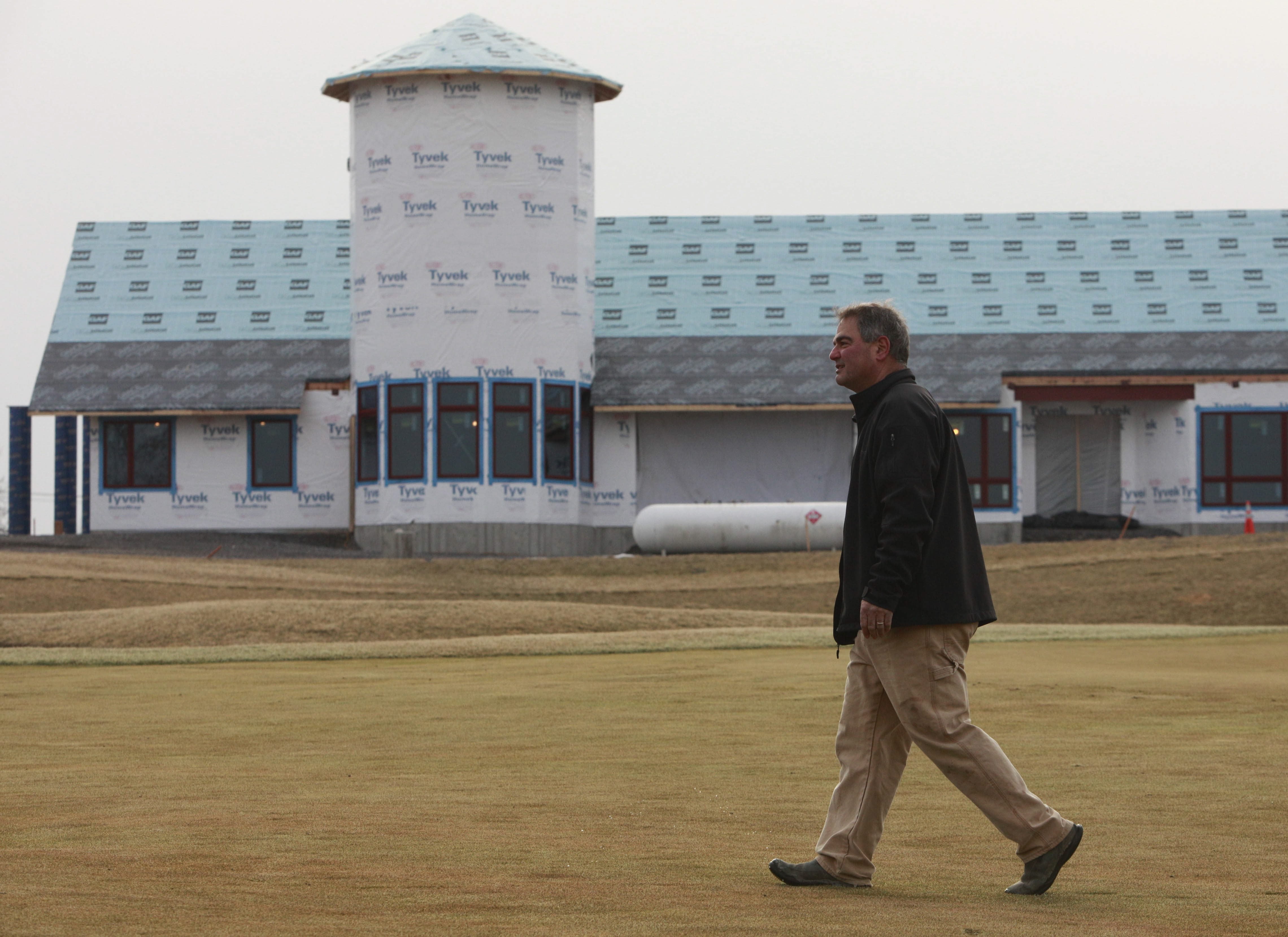 Attorney Ross Cellino, who bought the Harvest Hill Golf Course in Orchard Park last fall, walks across the approach to the 18th green. The new clubhouse – designed to evoke a barn with a silo – is under construction in the background.